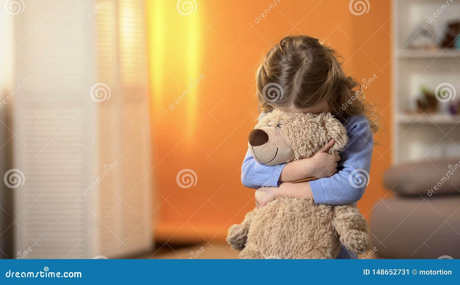 Schuw krullend meisjes verbergend gezicht achter favoriete teddybeer, kinderjarenpsychologie