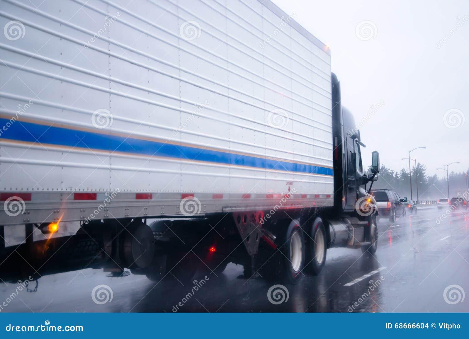 Schwärzen Sie halb LKW mit Refferanhänger auf dem Regnen der Landstraße
