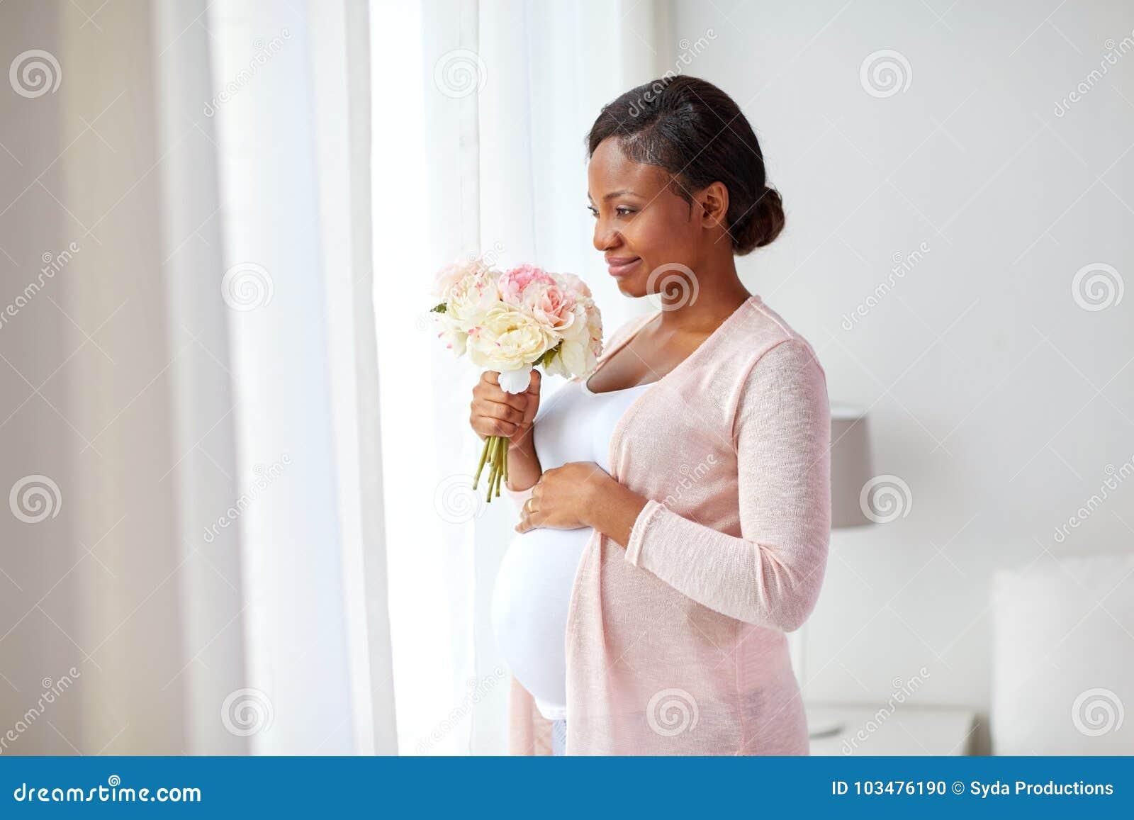 Schwangere Frau des glücklichen Afroamerikaners mit Blumen