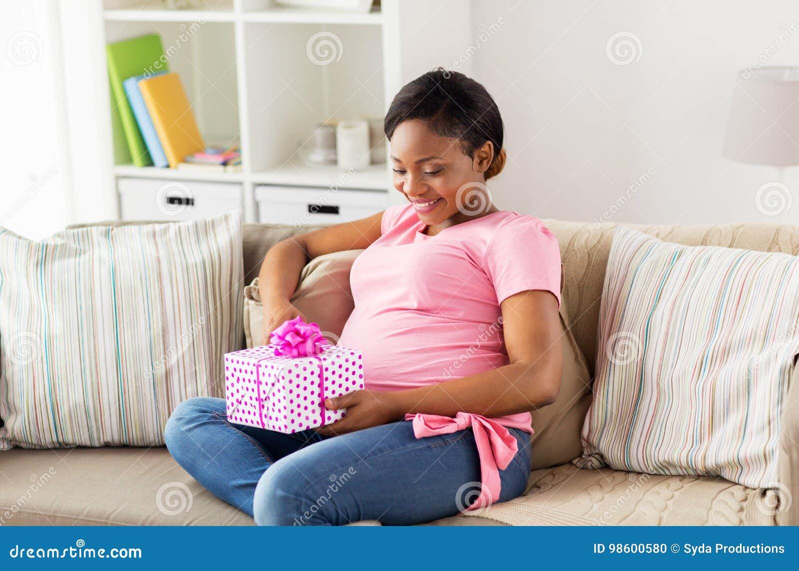Schwangere Frau des glücklichen Afroamerikaners mit Geschenk