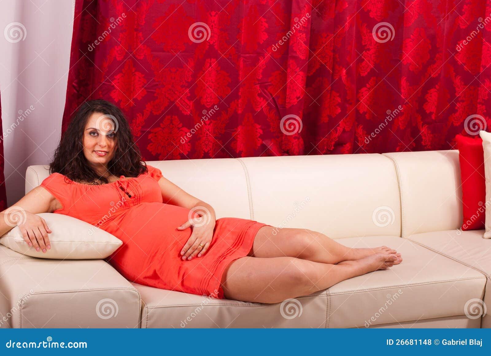 Schwangere Frau, die auf Couch liegt
