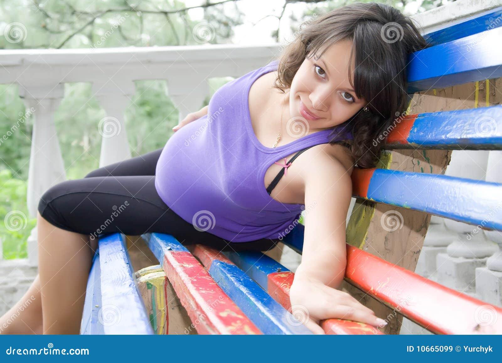 Schwangere Frau, die auf Parkbank sitzt