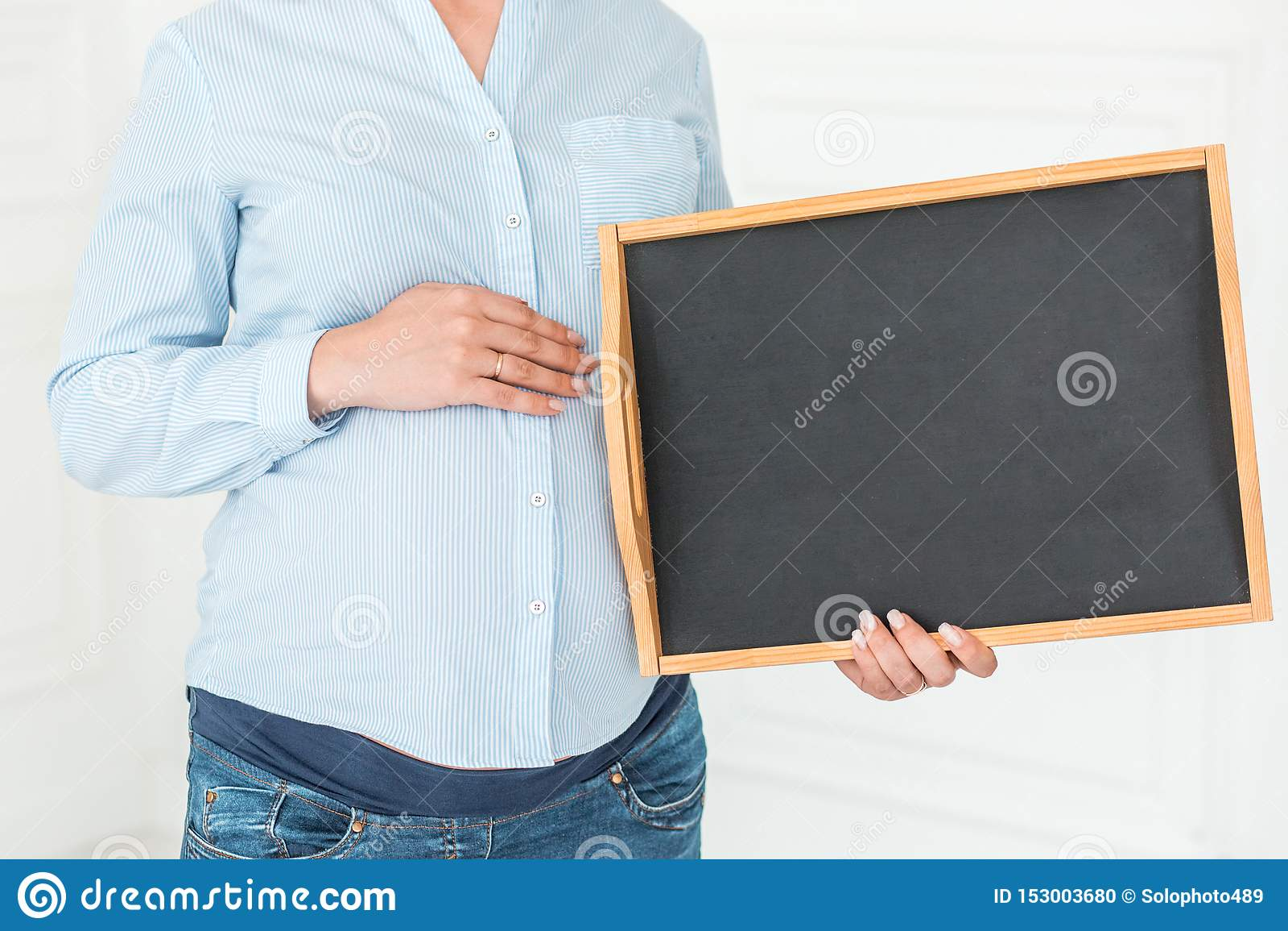 Schwangere Frau hält eine leere Tafel Nahaufnahme, Kopienraum, zuhause