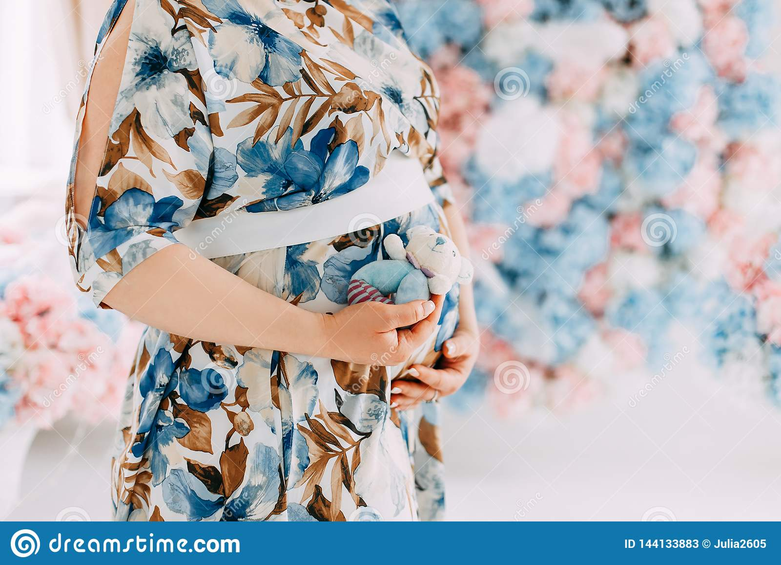 Schwangere Frau im empfindlichen blauen Kleid, das ihren Bauch streicht