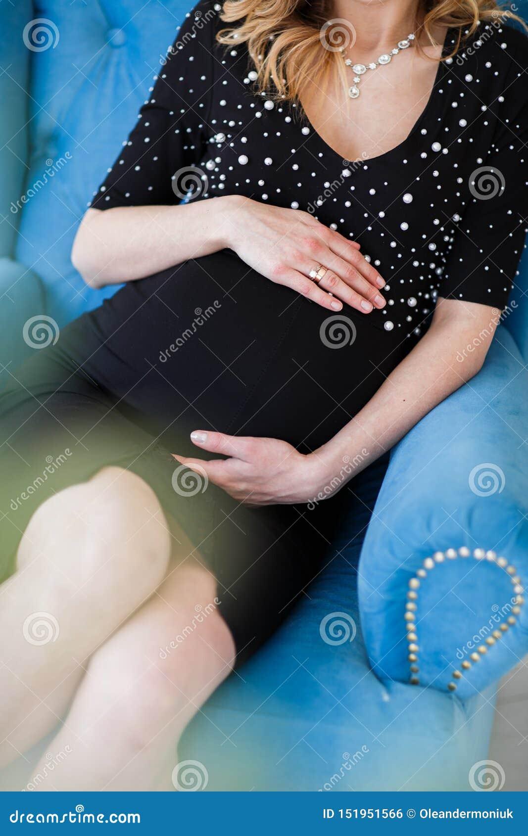 Schwangere Frau im schwarzen Kleid hält Hände auf Bauch auf einem weißen Hintergrund