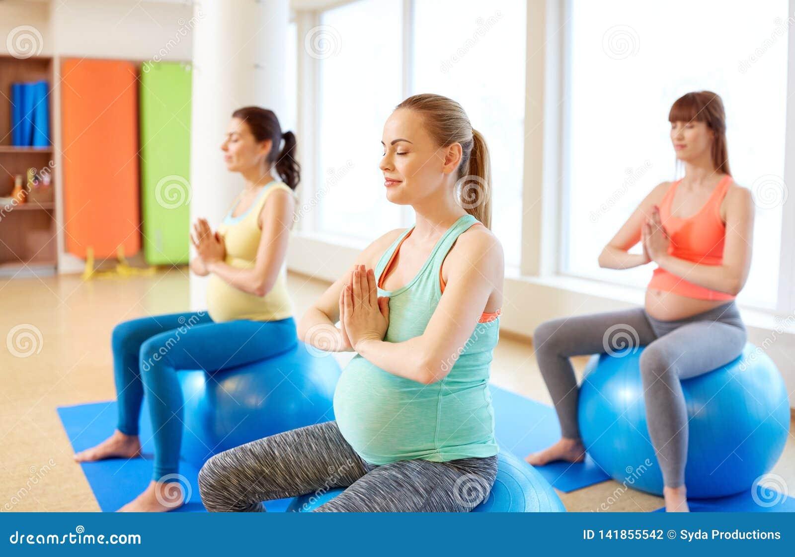 Schwangere Frauen, die auf Übungsbällen in der Turnhalle sitzen