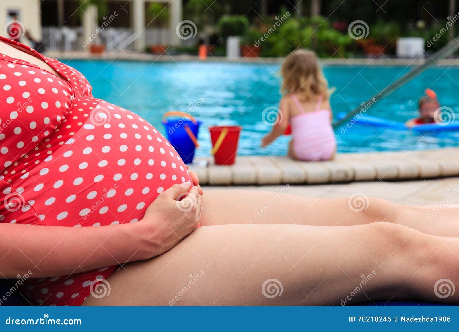 Schwangere Mutter entspannen sich durch das Pool, während Kinder mit Wasser spielen