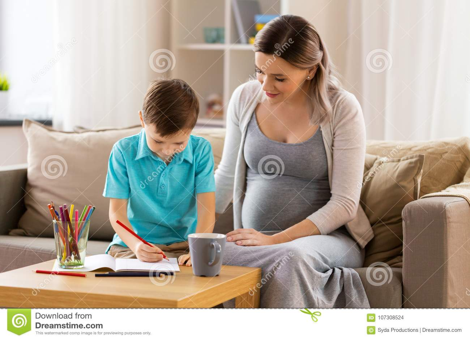 Schwangere Mutter und Sohn mit Arbeitsbuch zu Hause