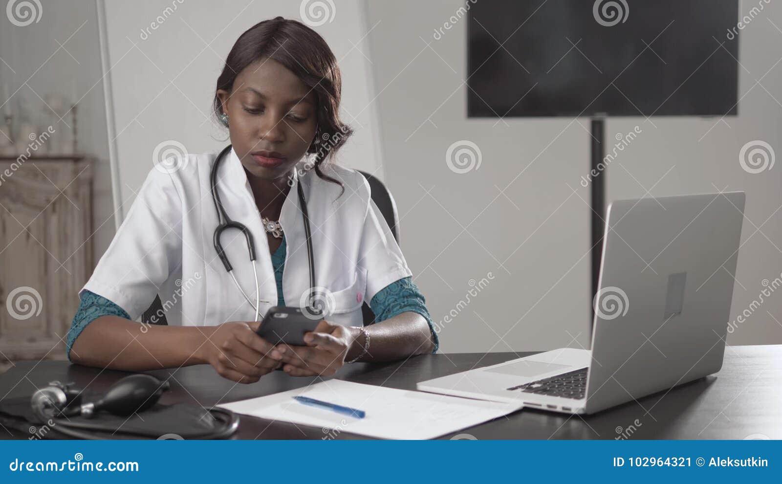 Schwarze Ärztin sitzt an einem Schreibtisch, der zur Kamera, Afroamerikanerkrankenschwesterarbeit über Laptop im Kabinett schaut,