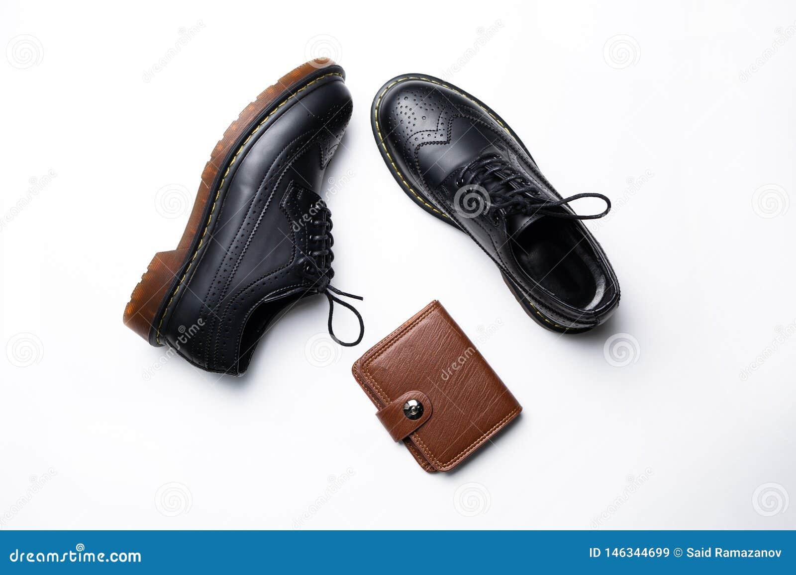 Schwarze lederne Derby-Schuhe mit Polyurethansohlen und ein brauner Geldbeutel mit einem Knopf auf einem wei?en Hintergrund