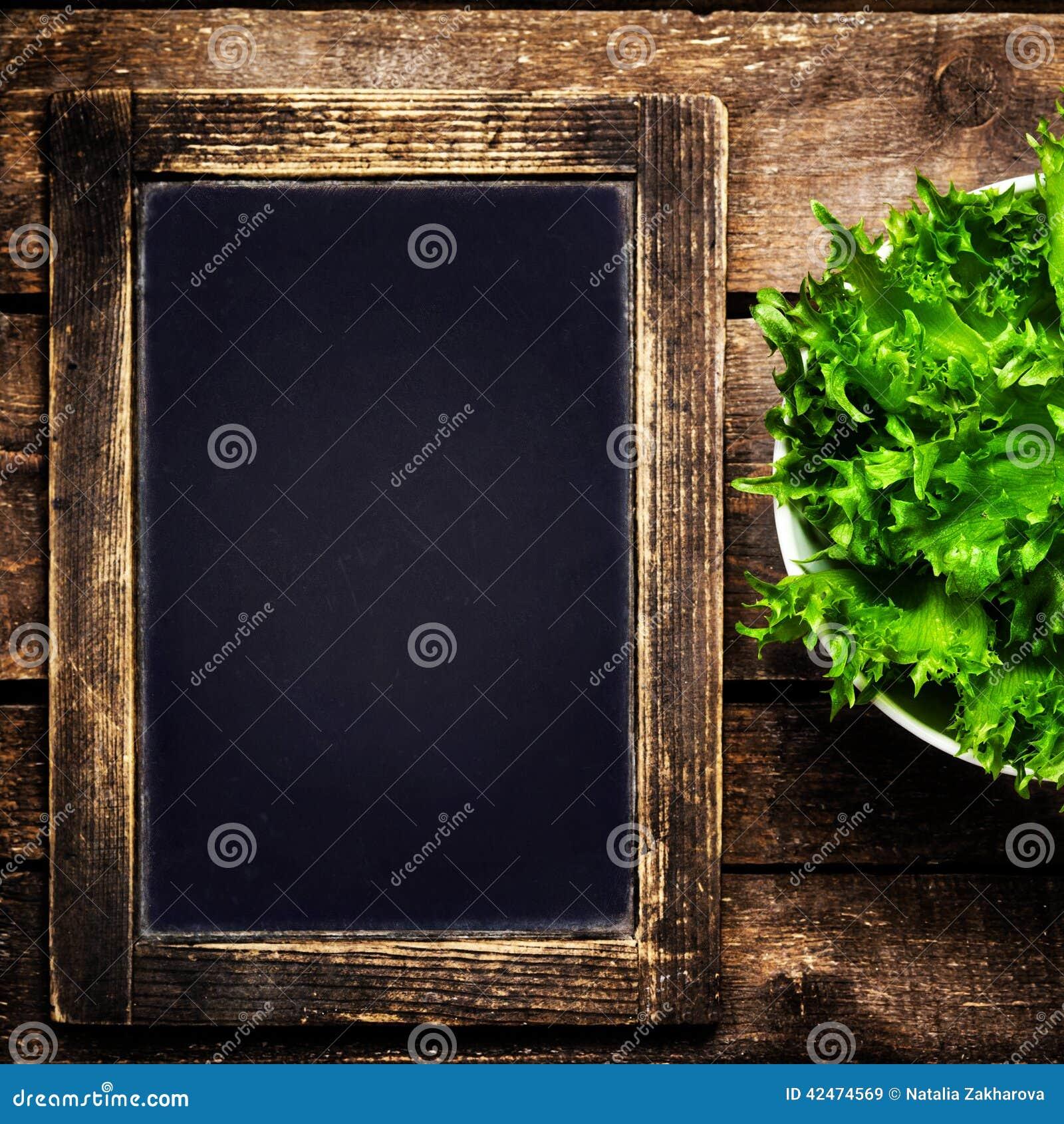 Schwarze Tafel für Menü und frischer Salat über hölzernem Hintergrund