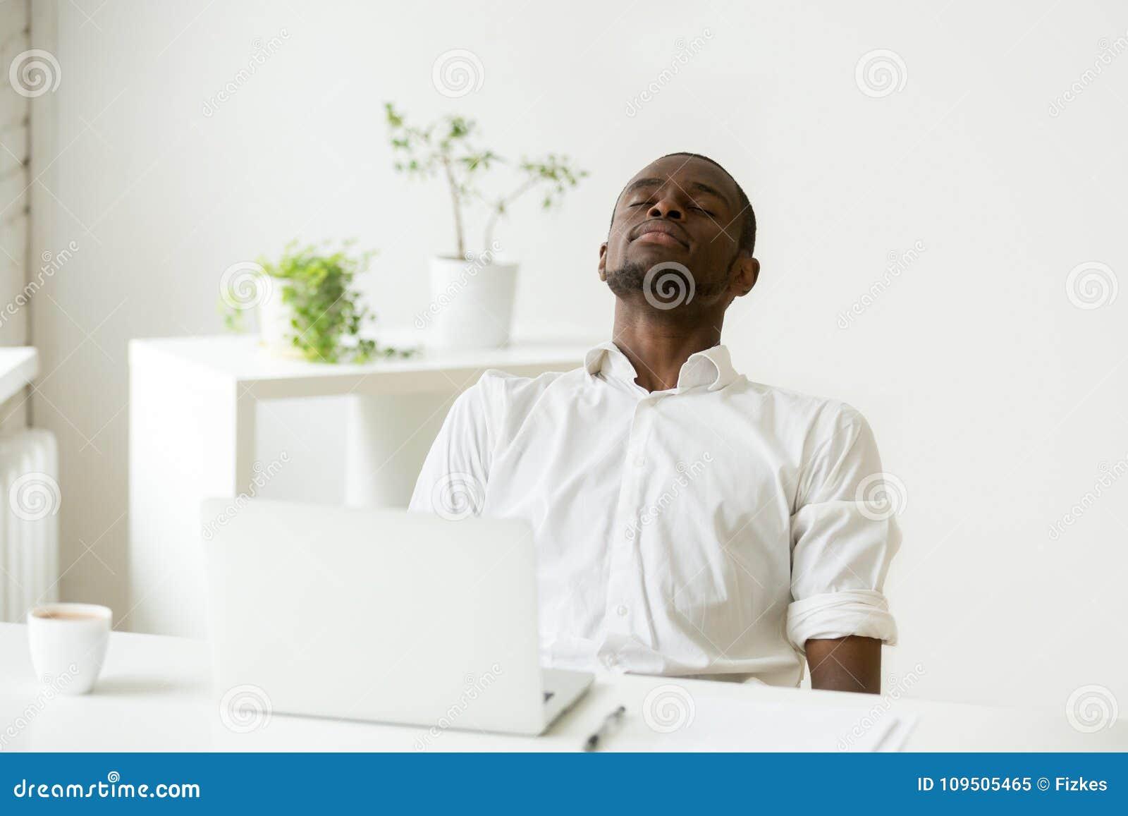 Schwarzer Angestellter, der die Pause tut Übung für Entspannung bei der Arbeit macht