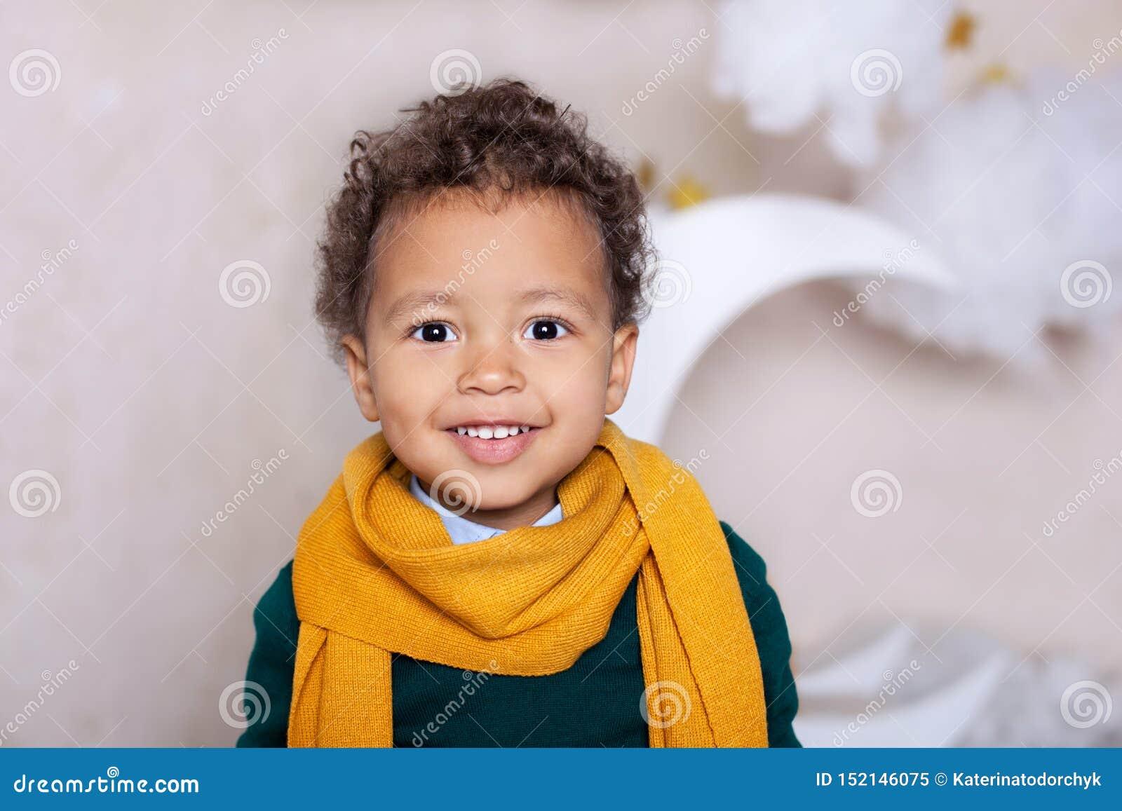 Schwarzer Jungenabschluß herauf Porträt Porträt eines netten lächelnden Jungen in einem gelben Schal das Baby l?chelt Wenig Afroa