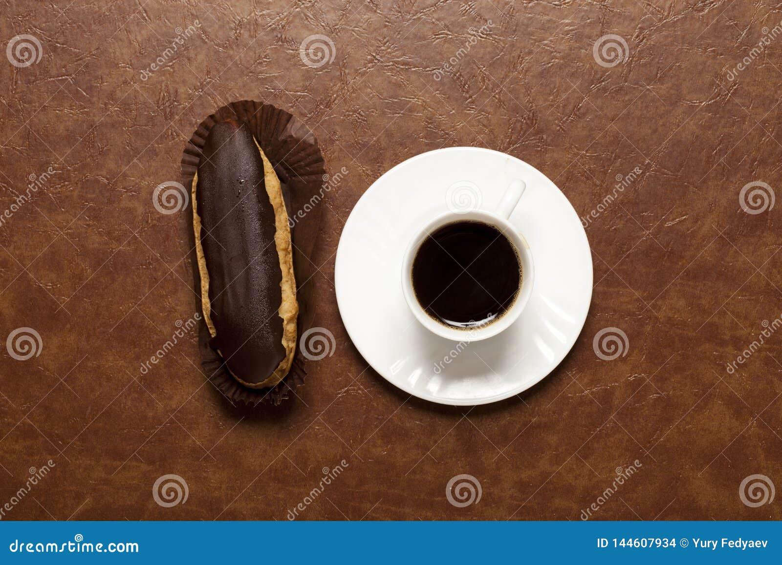 Schwarzer Kaffee, Schokolade Eclair, Kaffee in der weißen Schale, weiße Untertasse, auf brauner Tabelle, Eclair auf Stand
