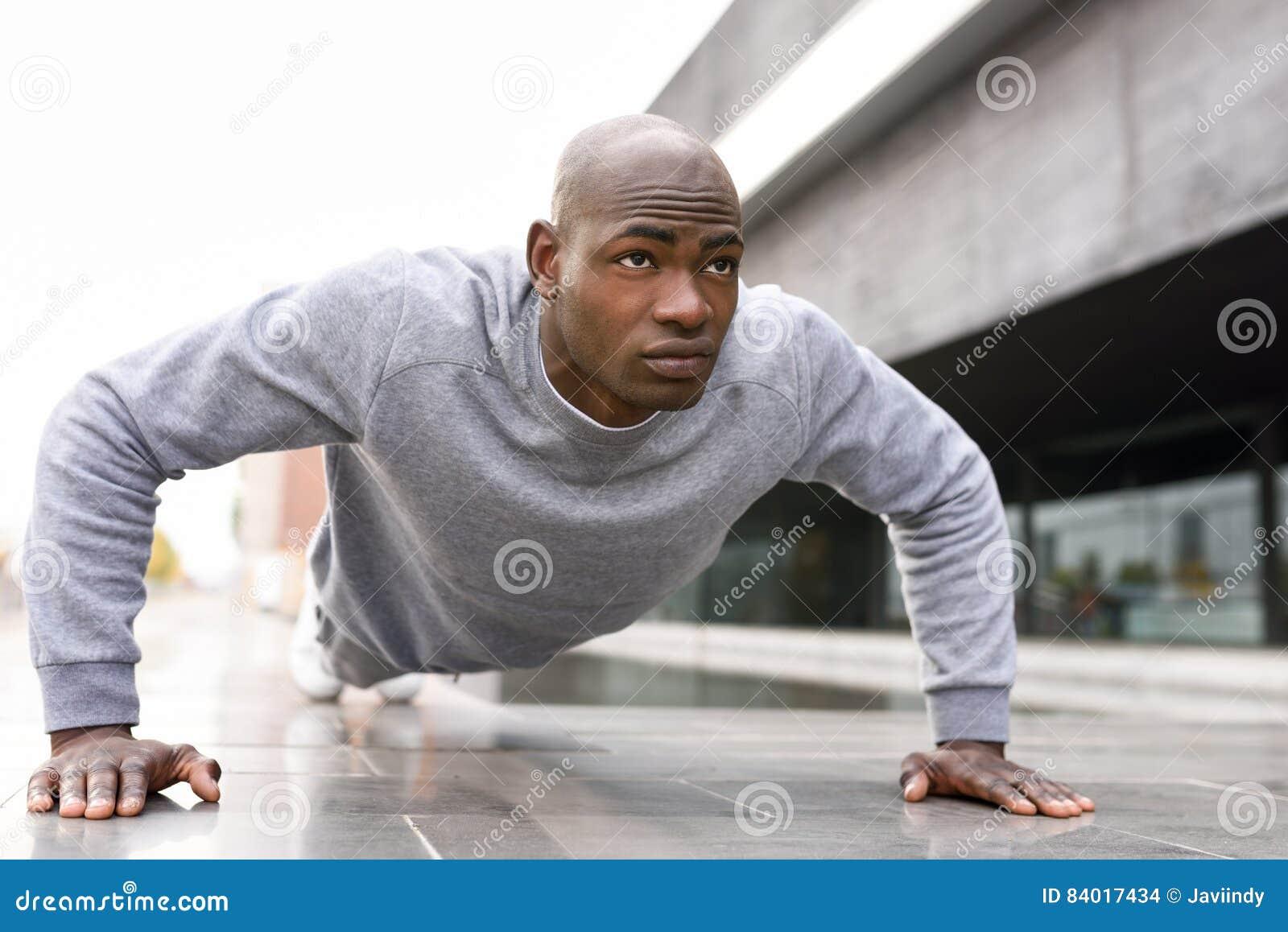 Schwarzer Mann der Eignung, den das Trainieren drücken, ups in städtischen Hintergrund