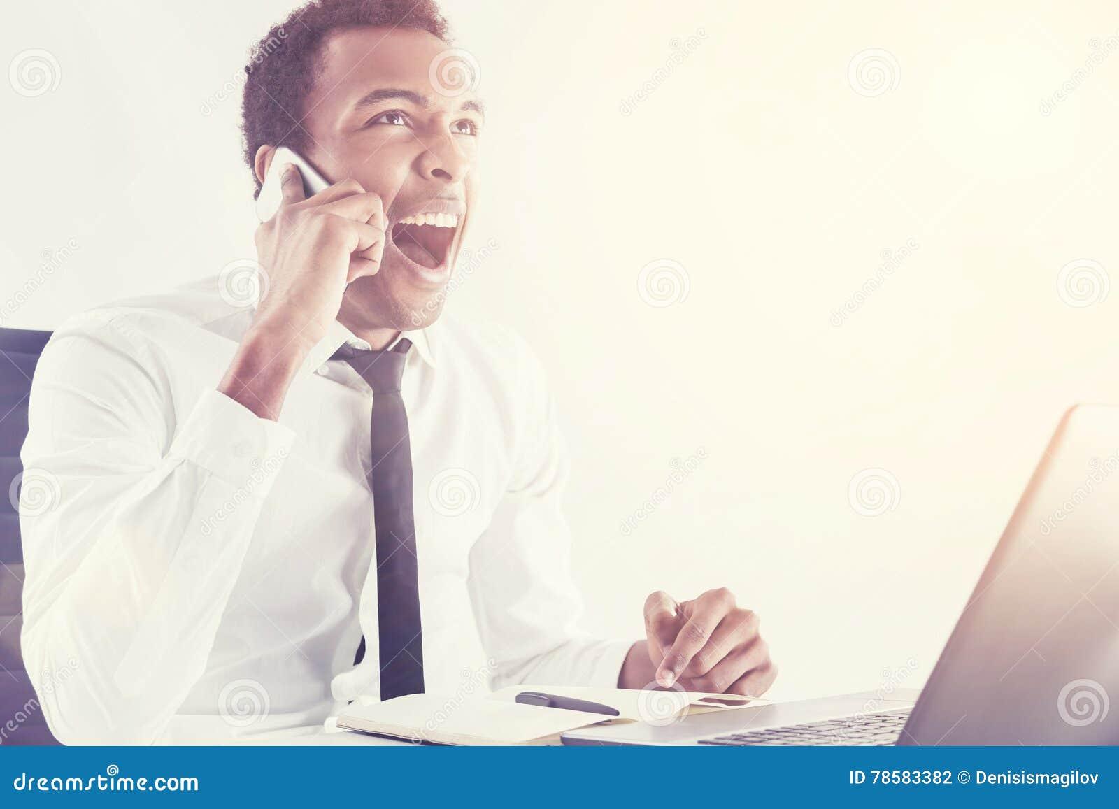 Schwarzer Mann, der am Handy schreit