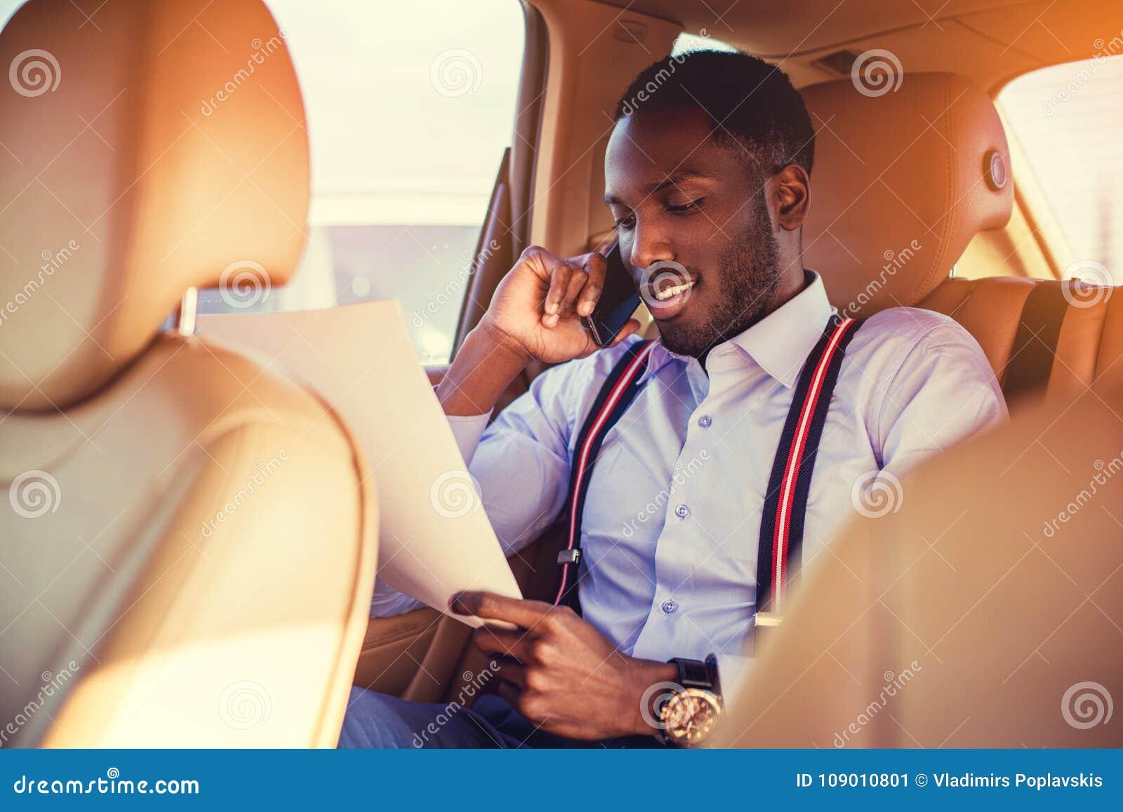 Schwarzer Mann, der Smartphone in einem Auto verwendet