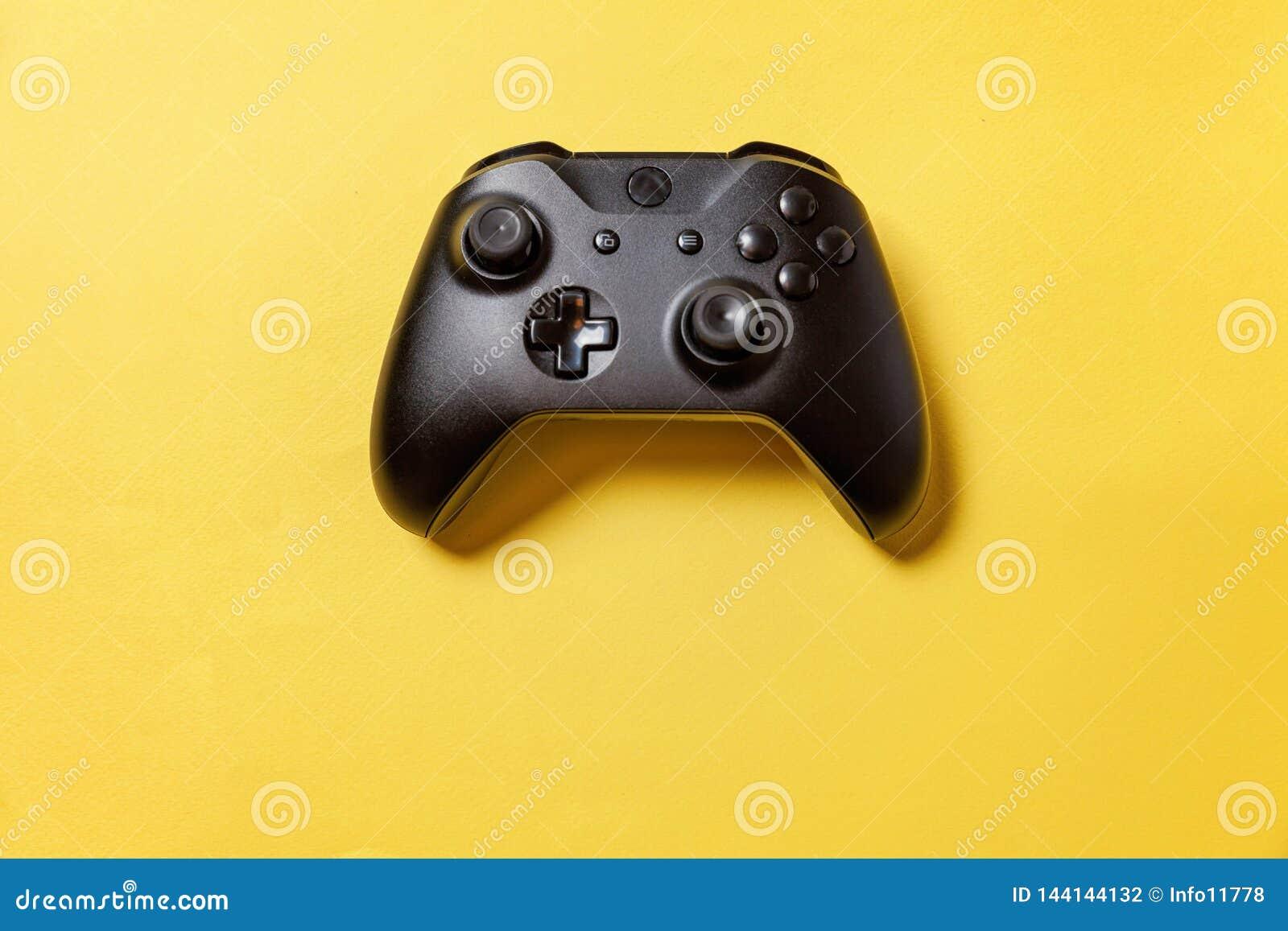 Schwarzer Steuerknüppel auf gelbem Hintergrund Computerspielwettbewerbsvideospielsteuerkonfrontationskonzept