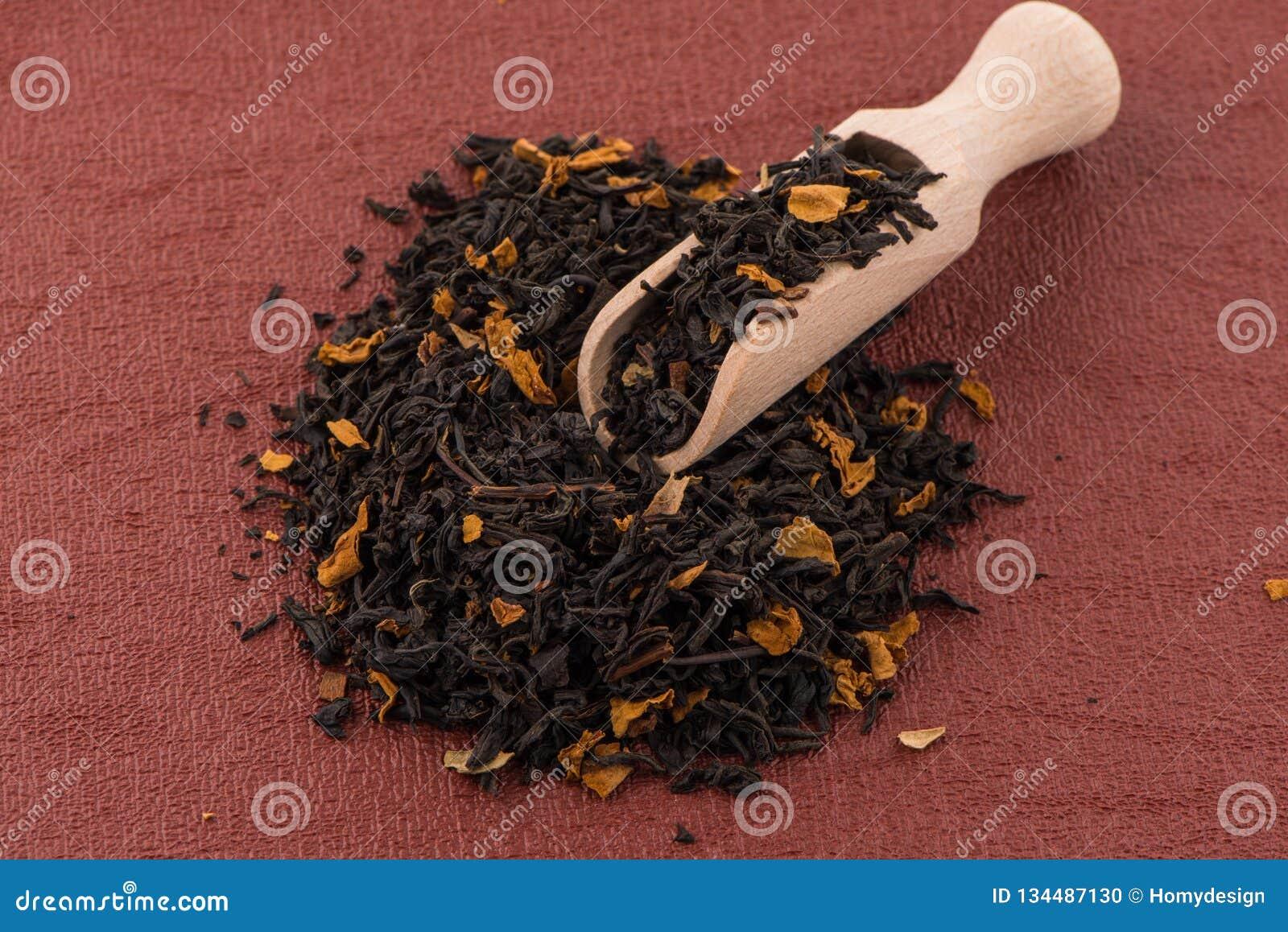 Schwarzer trockener Tee mit einem hölzernen Löffel