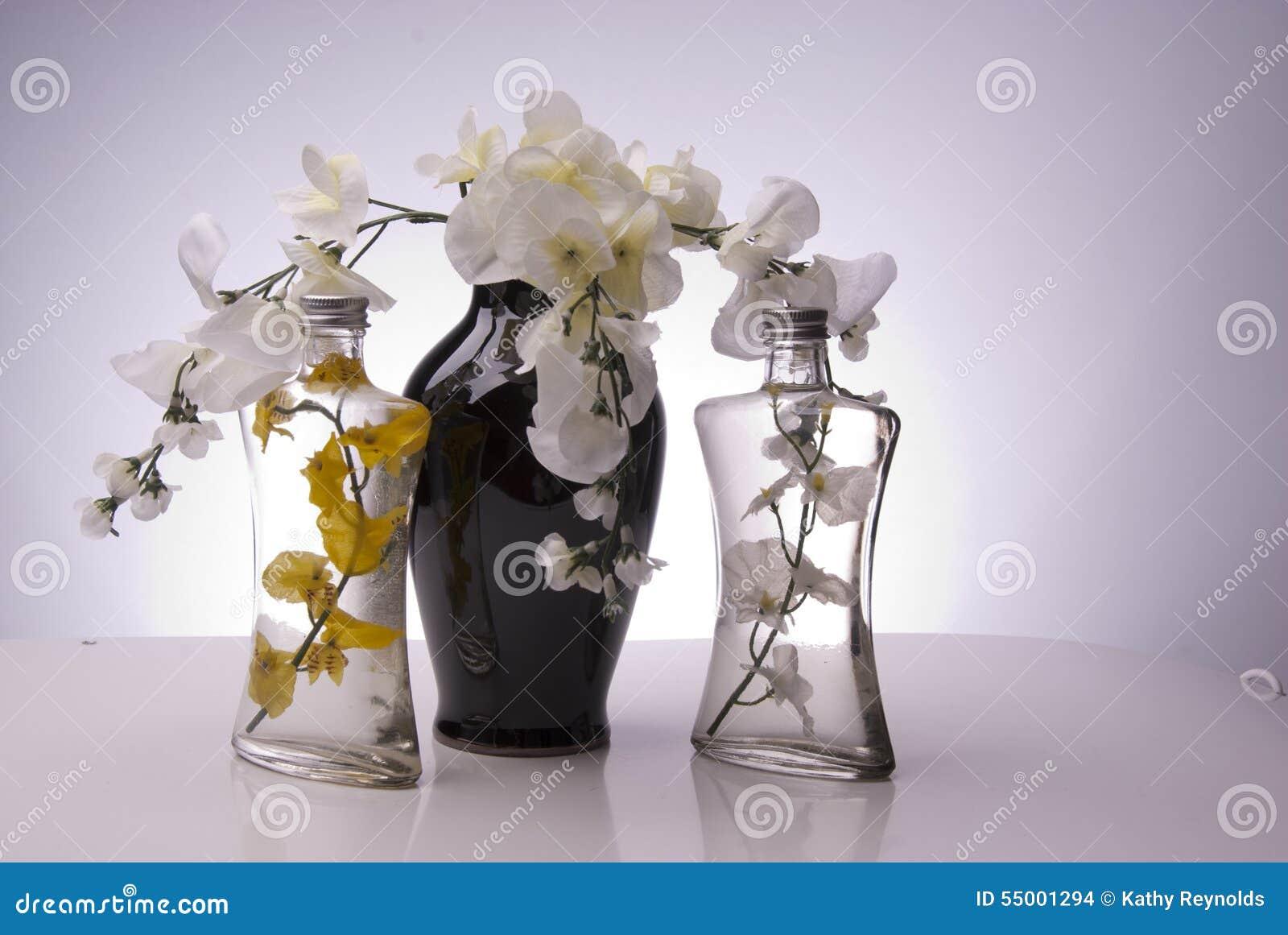 Schwarzer Vase mit klaren Flaschen und Blumen
