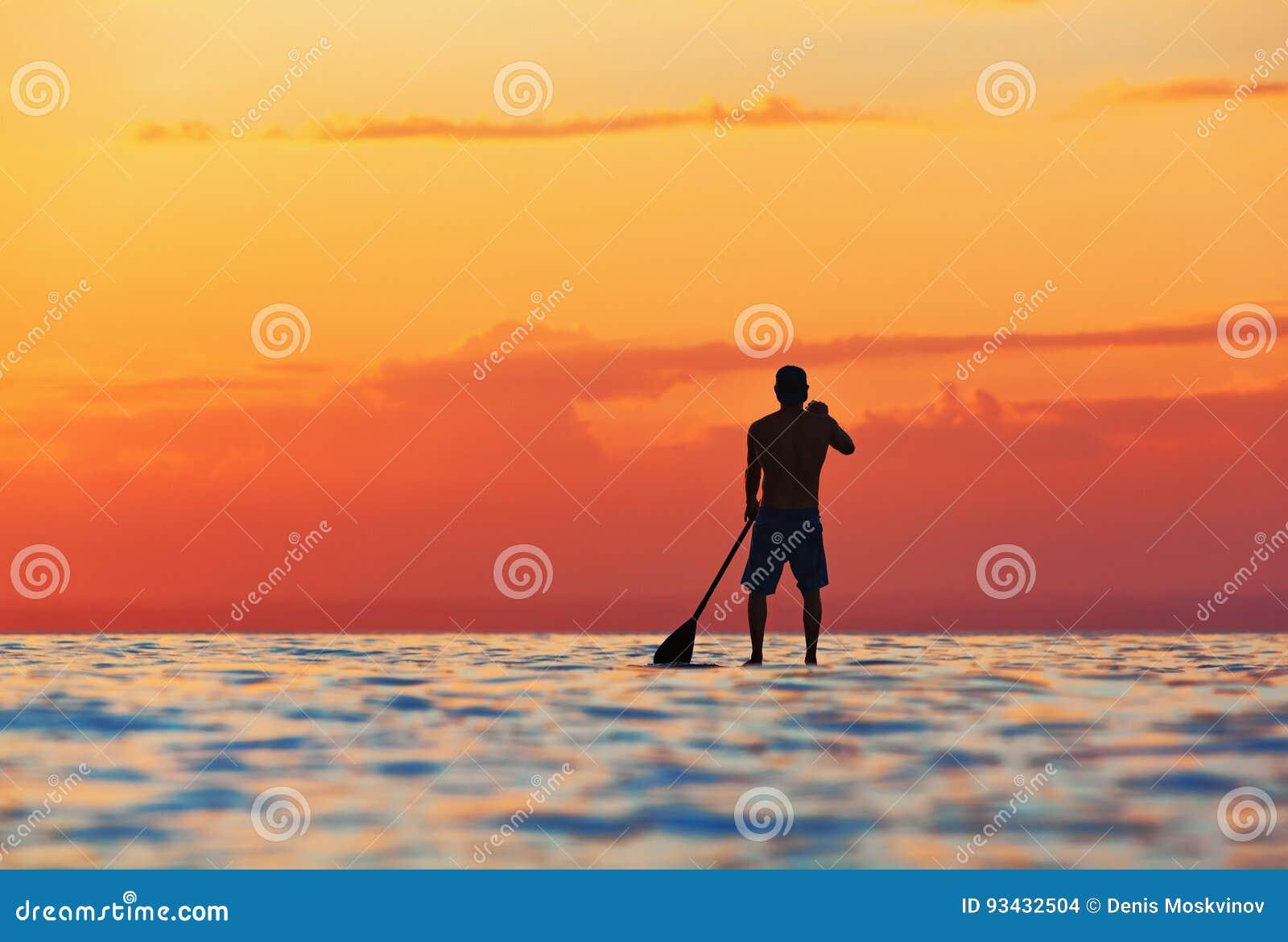 Schwarzes Sonnenuntergangschattenbild des Paddelinternatsschülers stehend auf SUP