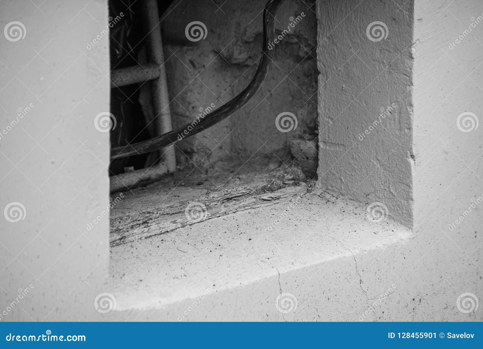 Schwarzweiss-Foto eines elektrischen Drahtes, der vom Keller eines Gebäudes kommt