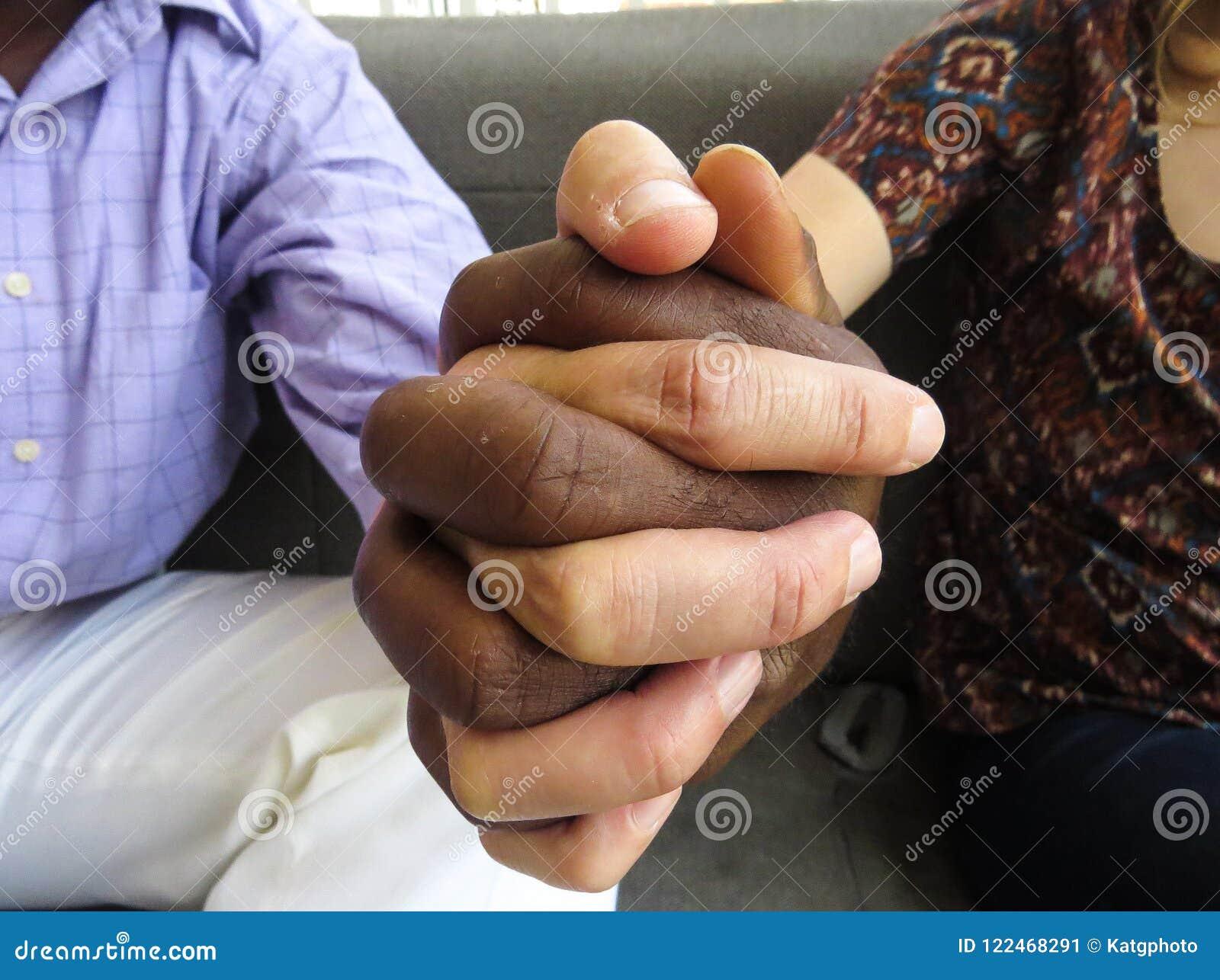 Schwarzweiss-Hände, die zusammen Teamwork und Verschiedenartigkeit zeigen