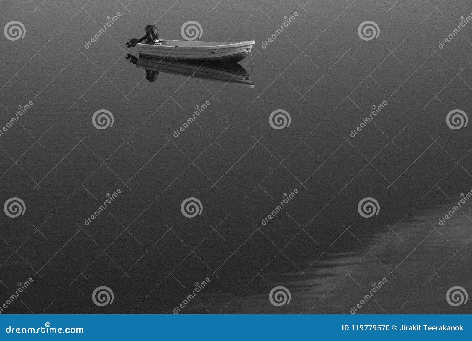 Schwarzweiss-klassisch altes körniges Foto des Bootes und seine klare Reflexion auf dem See tauchen auf