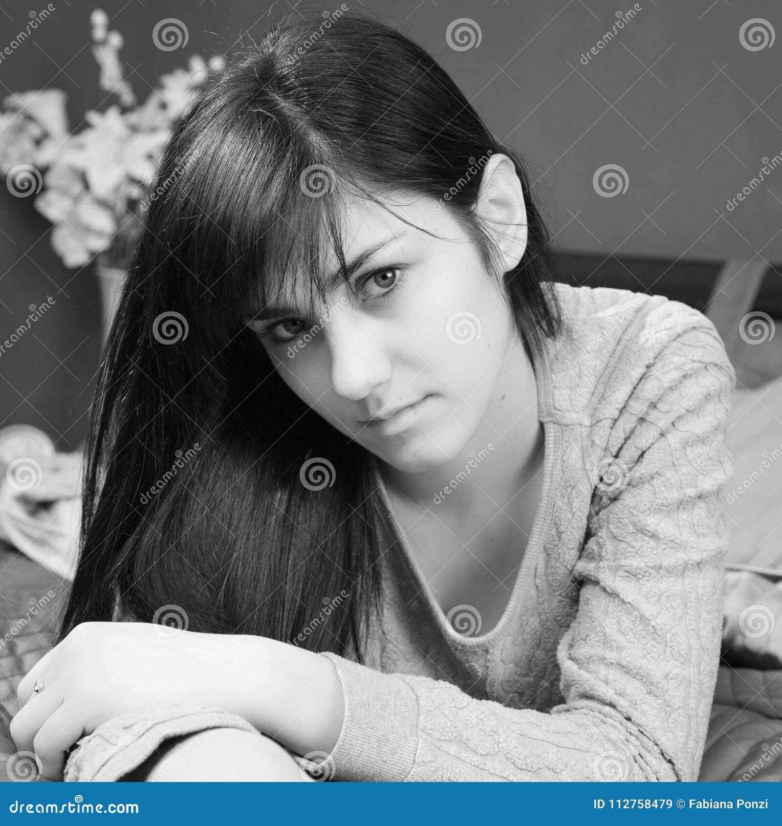 Schwarzweiss-Porträt der netten Schönheit liegend auf Bett