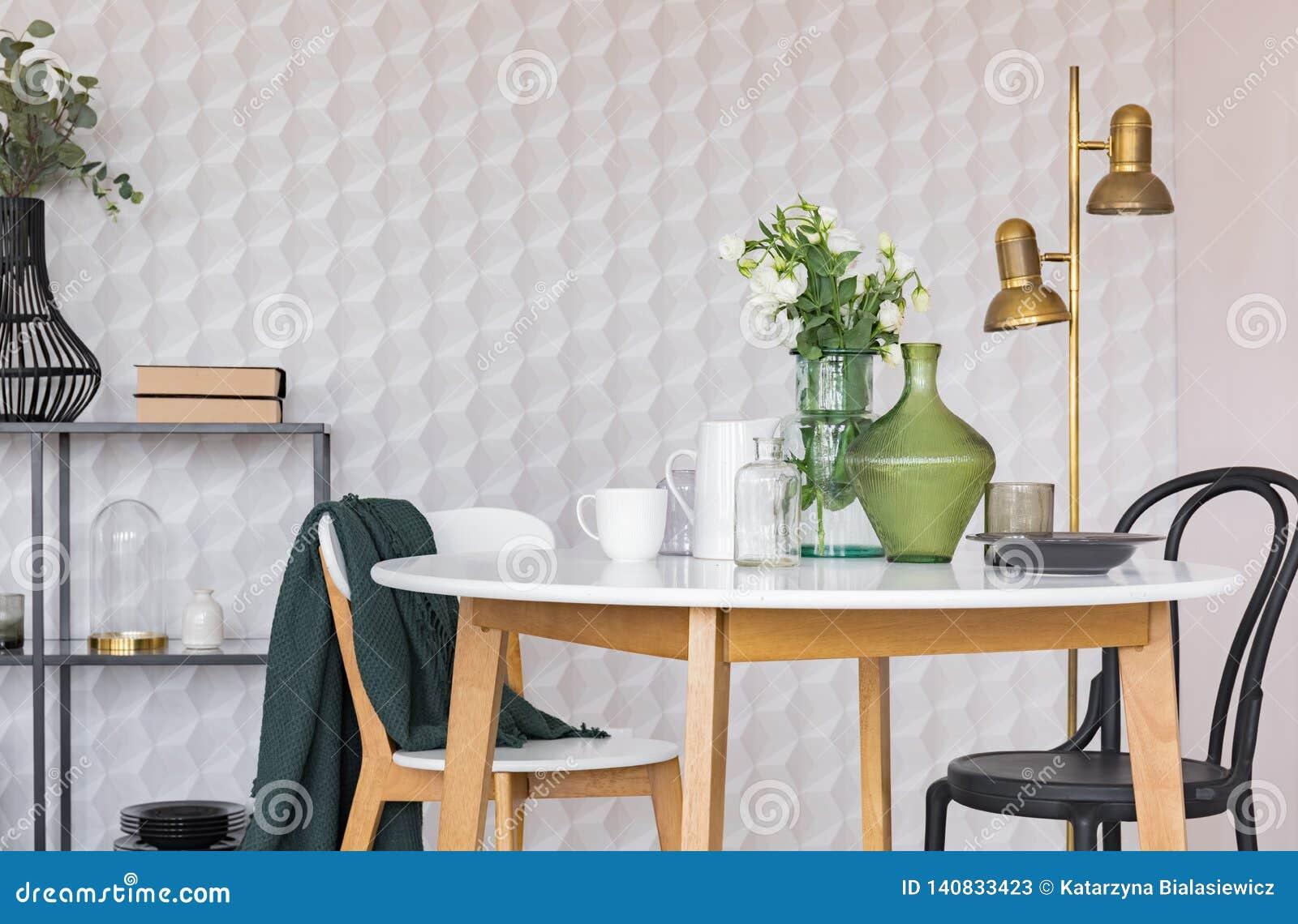 Schwarzweiss-Stuhl am Holztisch im Esszimmer Innen mit Blumen und Goldlampe Reales Foto