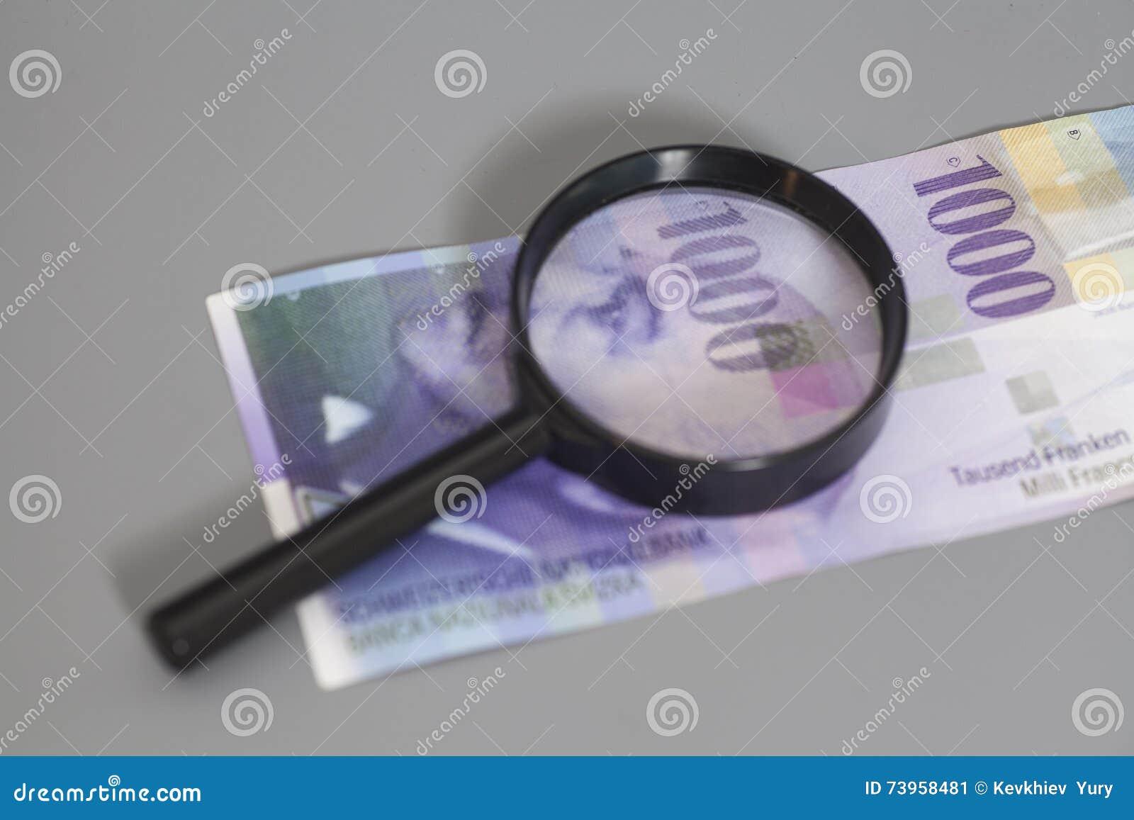 Schweizare 1000 franc sedlar under förstoringsglaset