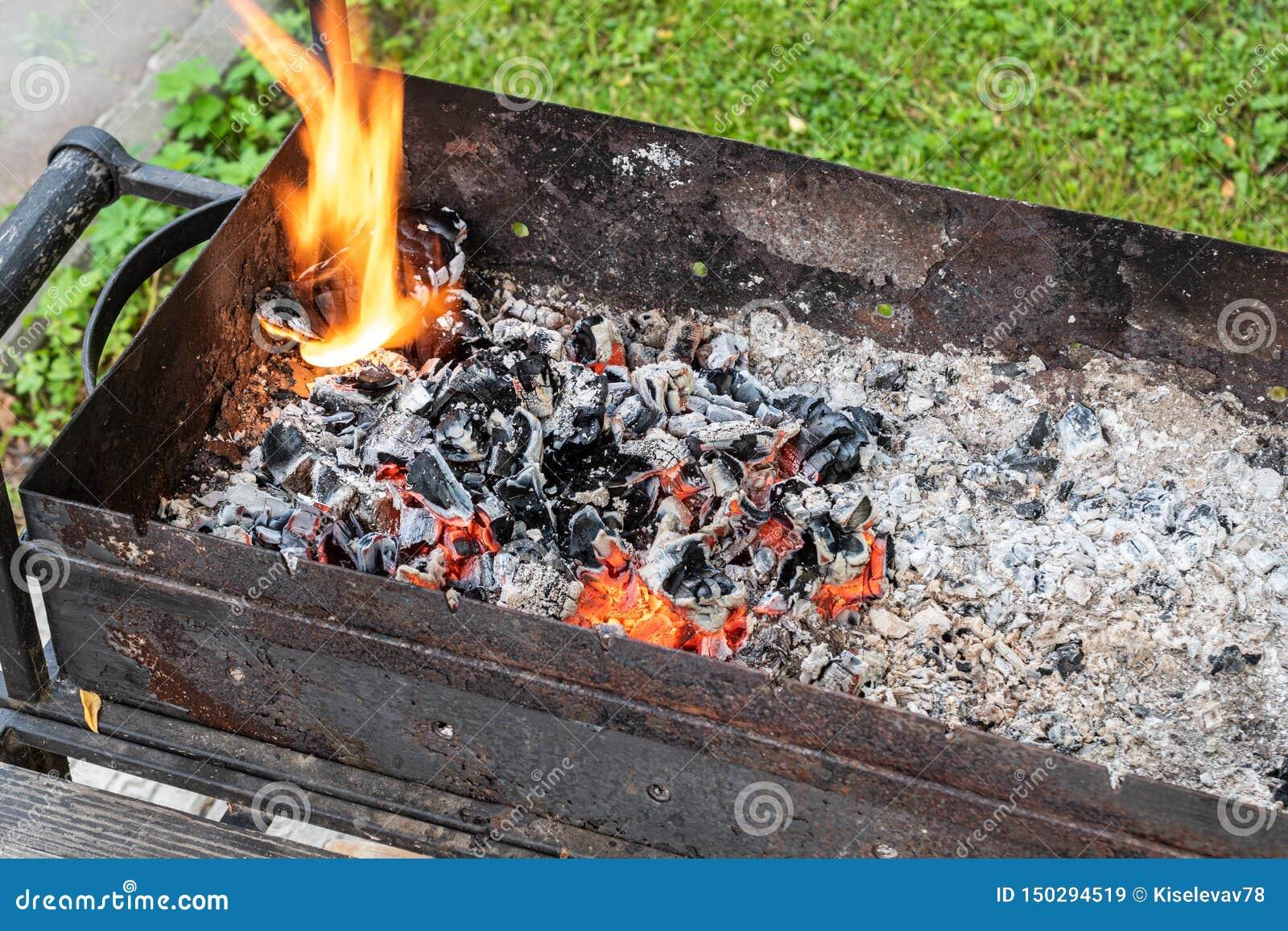 Schwelende Kohle in einem alten rostigen Grill Vorbereiten f?r ein Picknick