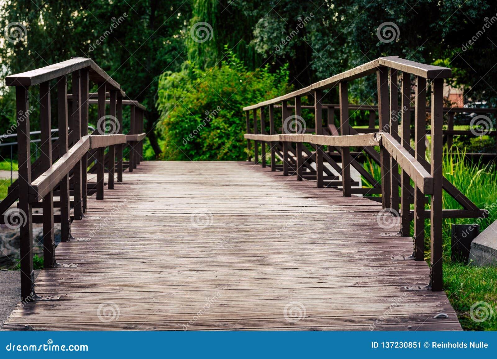 Schwermütiges Foto der Wodden-Brücke in einem Park, zwischen dem Holz - Desaturated, Weinlese-Blick