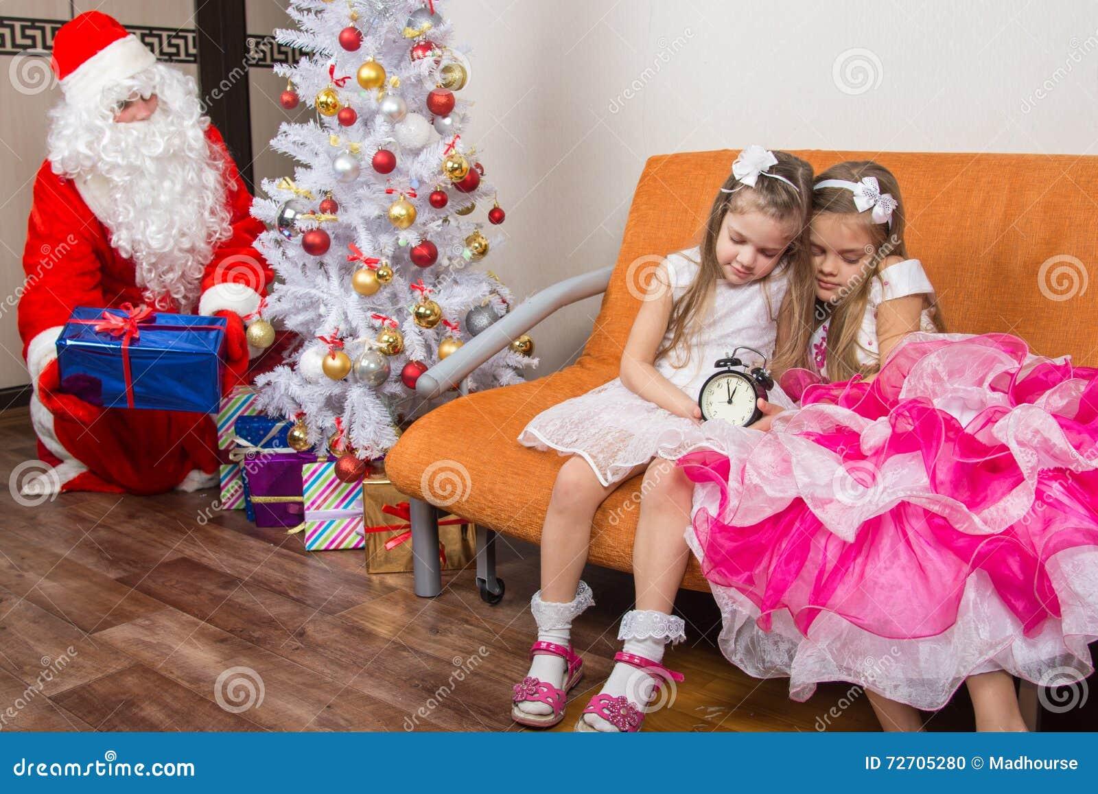Schwestern schliefen beim Warten auf Santa Claus ein, die ruhig Geschenke unter den Weihnachtsbaum setzte