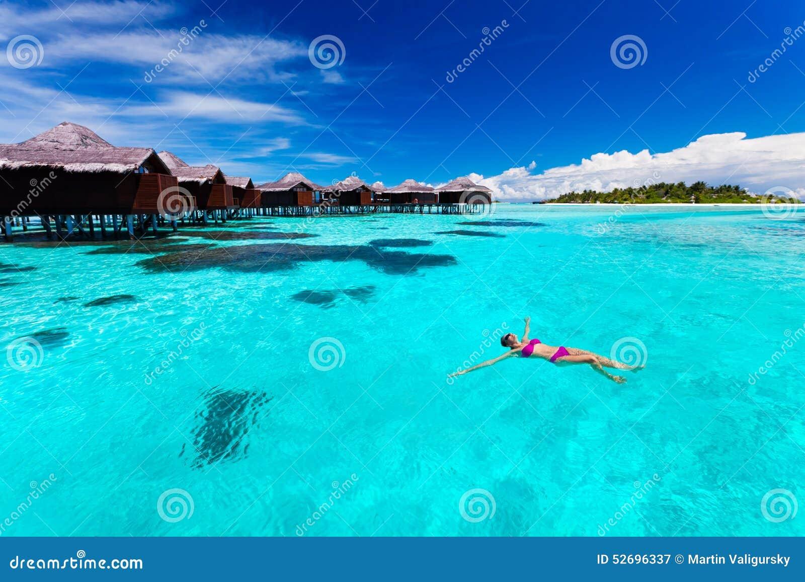 Schwimmen der jungen Frau von der Hütte in der tropischen Lagune