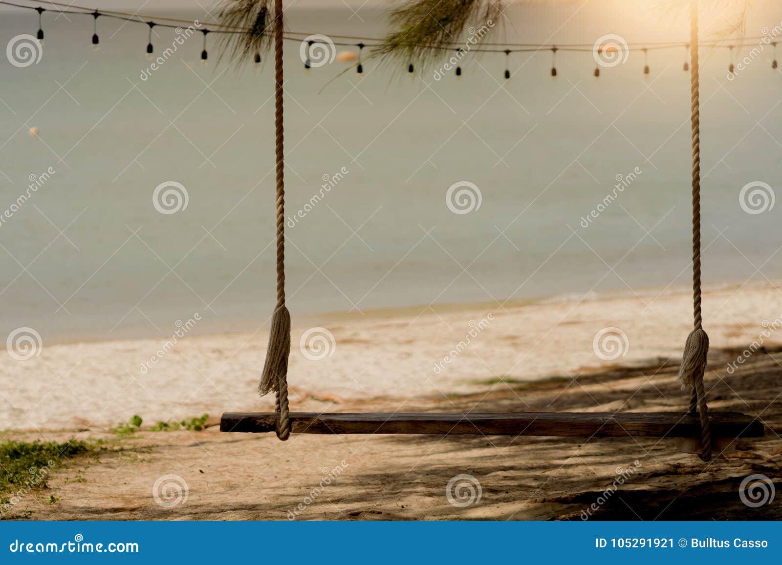 Schwingen auf dem Strand mit Sonnenuntergang