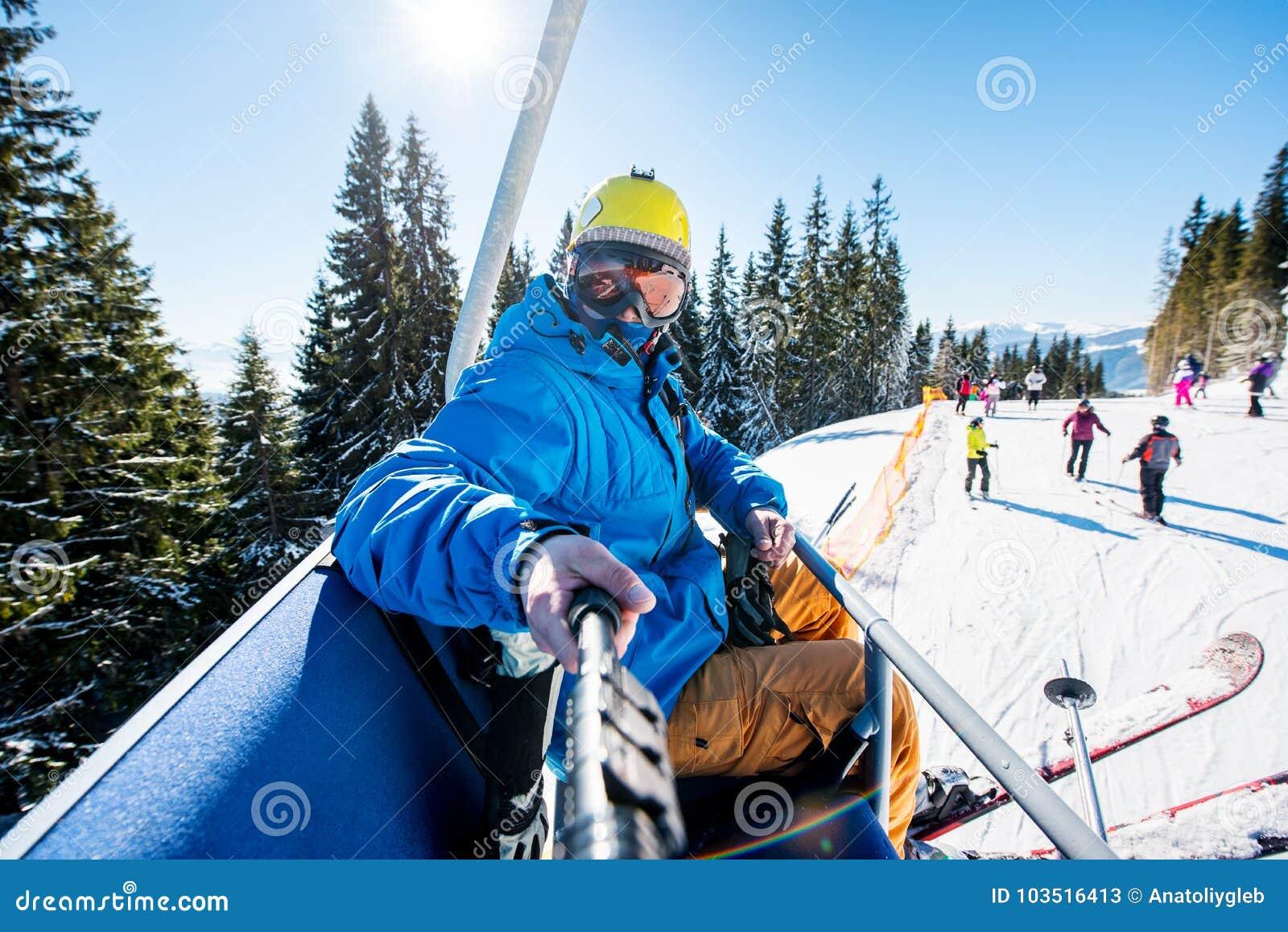 Sciatore maschio che per mezzo del bastone del selfie che prende le foto mentre sciando