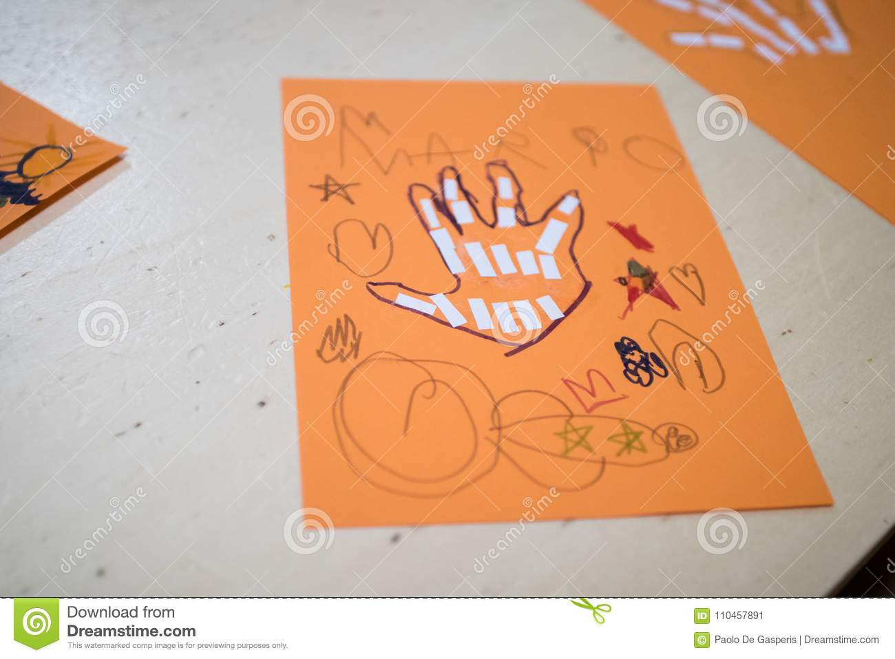 scientific activity for children, drawing and collage of the bones of the hand. On a decorated orange sheet a hand was drawn and