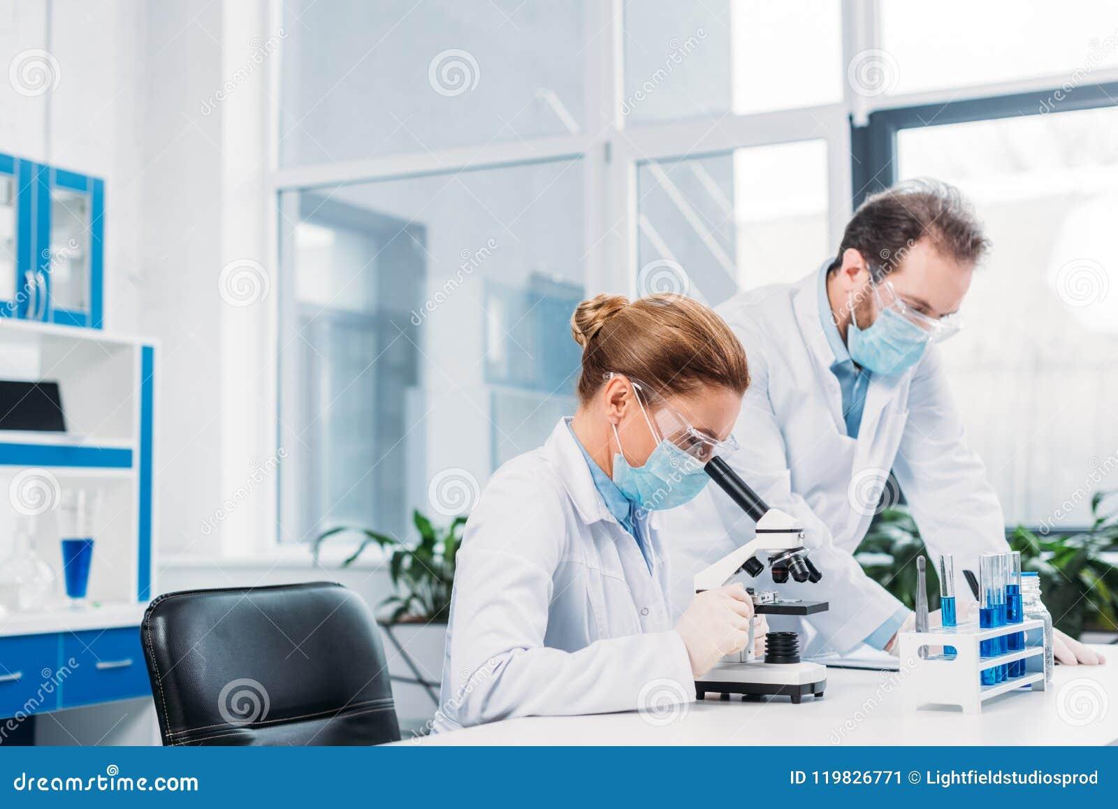 Scientifiques dans les masques médicaux et lunettes travaillant à la recherche scientifique