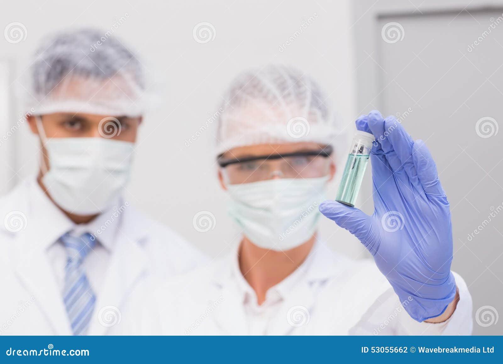 Scientifiques examinant le précipité vert dans le tube