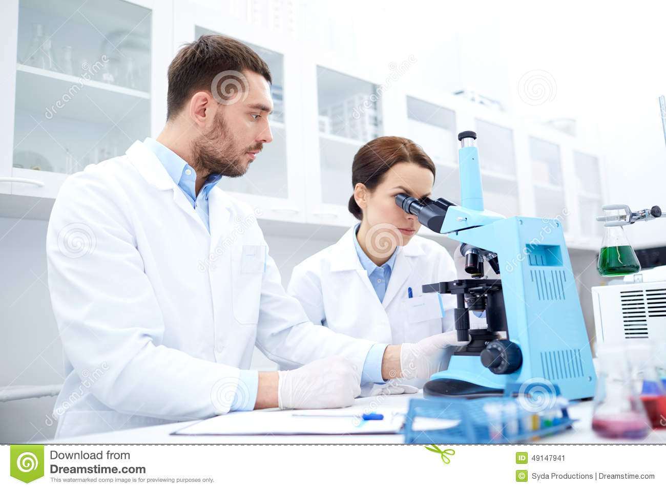 Scientists With Clipboard And Microscope In Lab Stock Photo ...