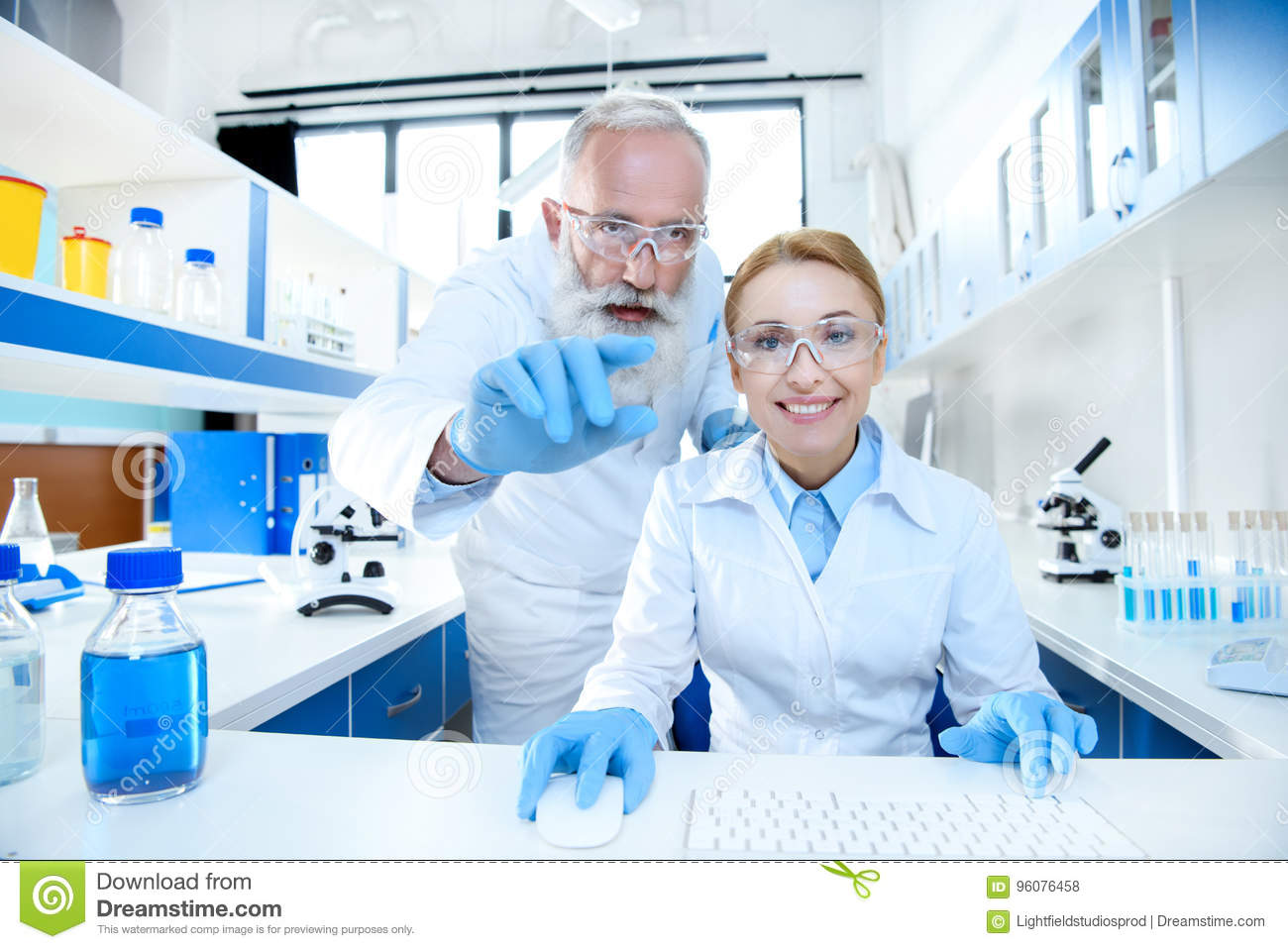 Scientists in protective eyeglasses working together in lab and pointing at camera