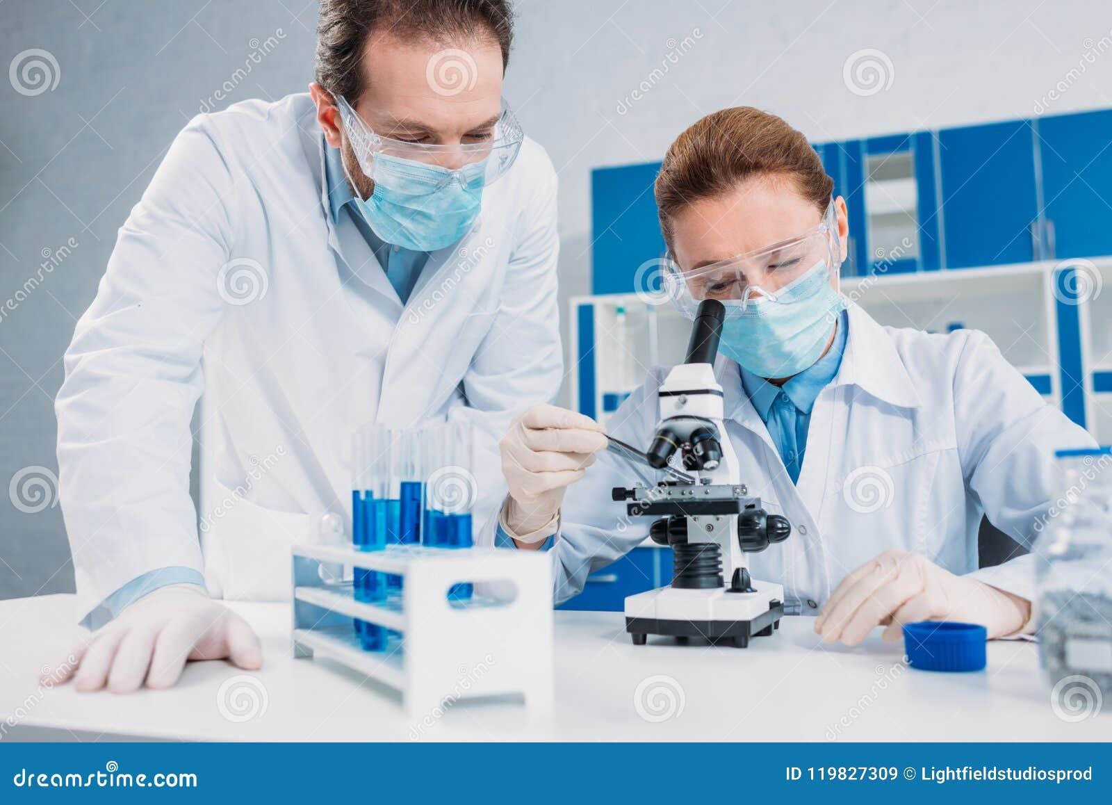 Scienziati in camice, in guanti medici ed in occhiali di protezione facenti insieme ricerca scientifica