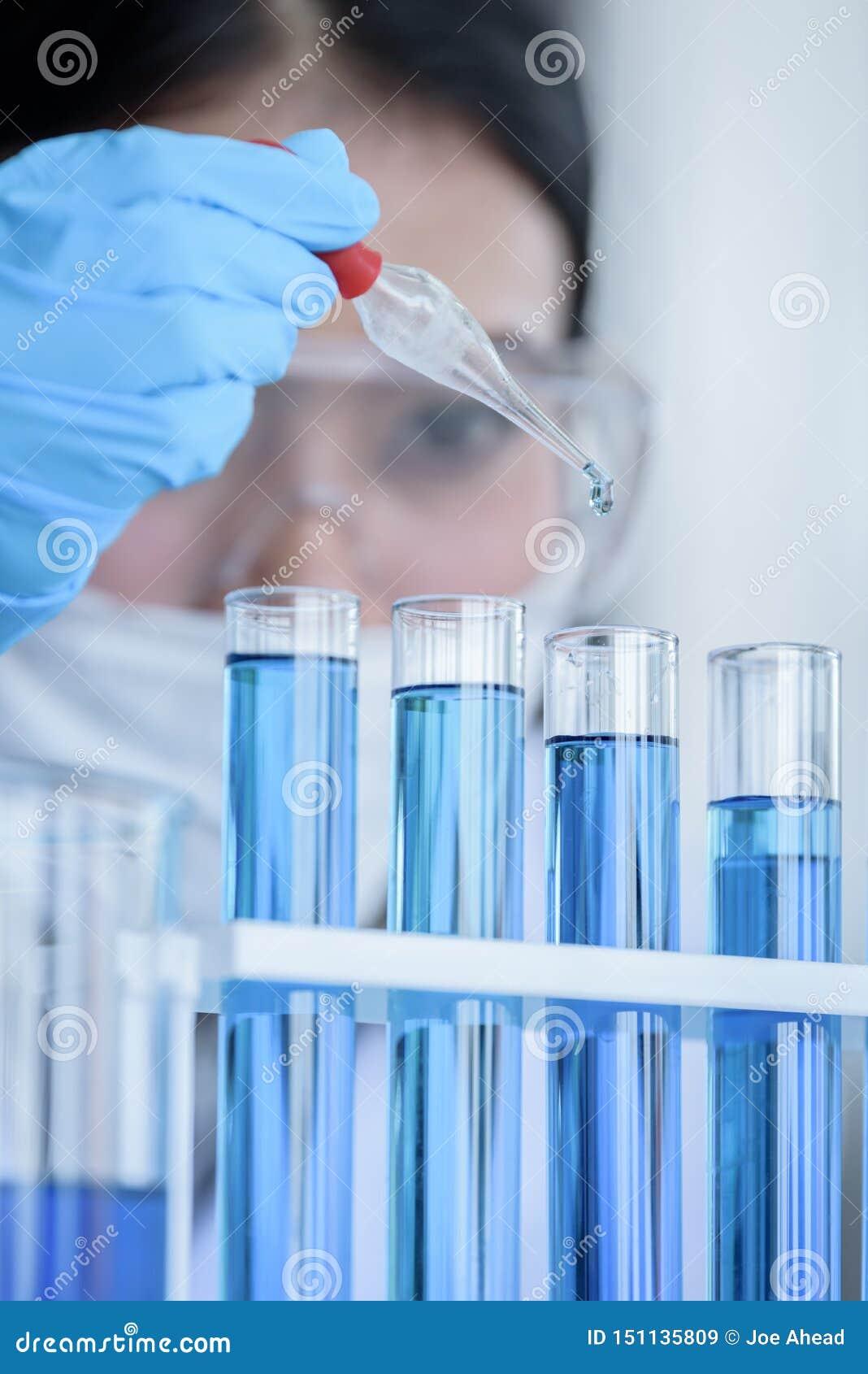 Scienziato asiatico dello studente della ragazza che ricerca e che impara in un laboratorio