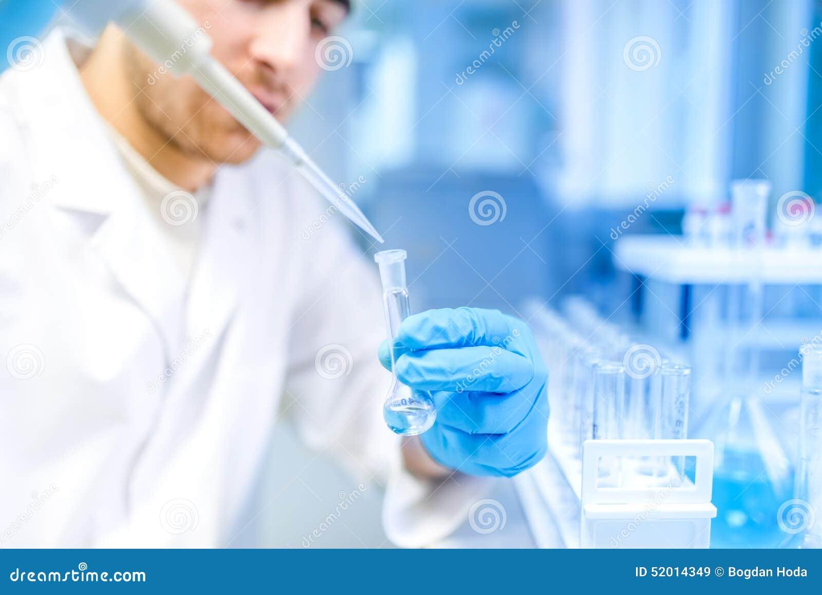 Scienziato che utilizza strumento medico per l estrazione di liquido dai campioni nel laboratorio speciale o nella stanza medica