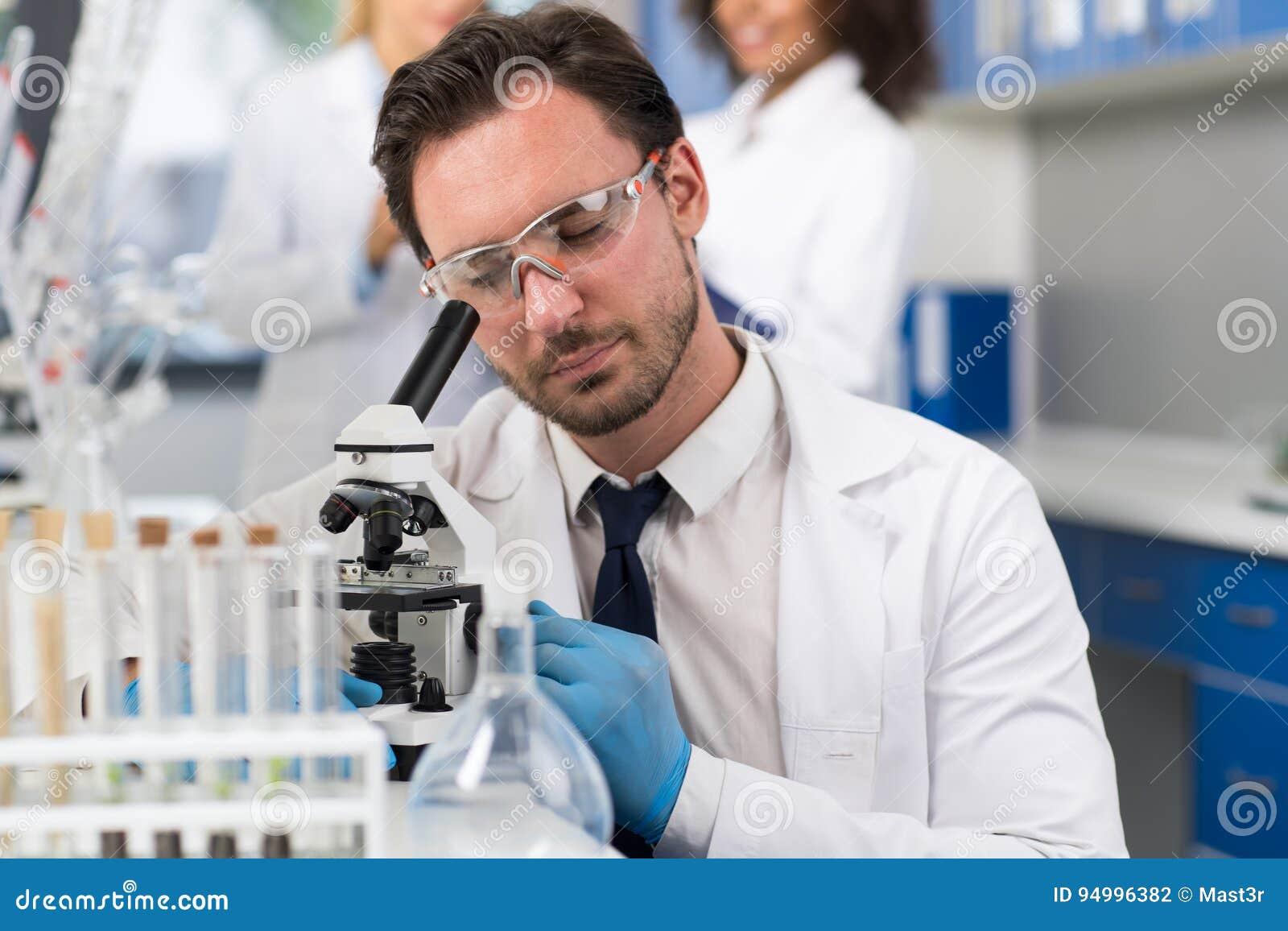 Scienziato Looking Through Microscope in laboratorio, ricercatore maschio Doing Research Experiments