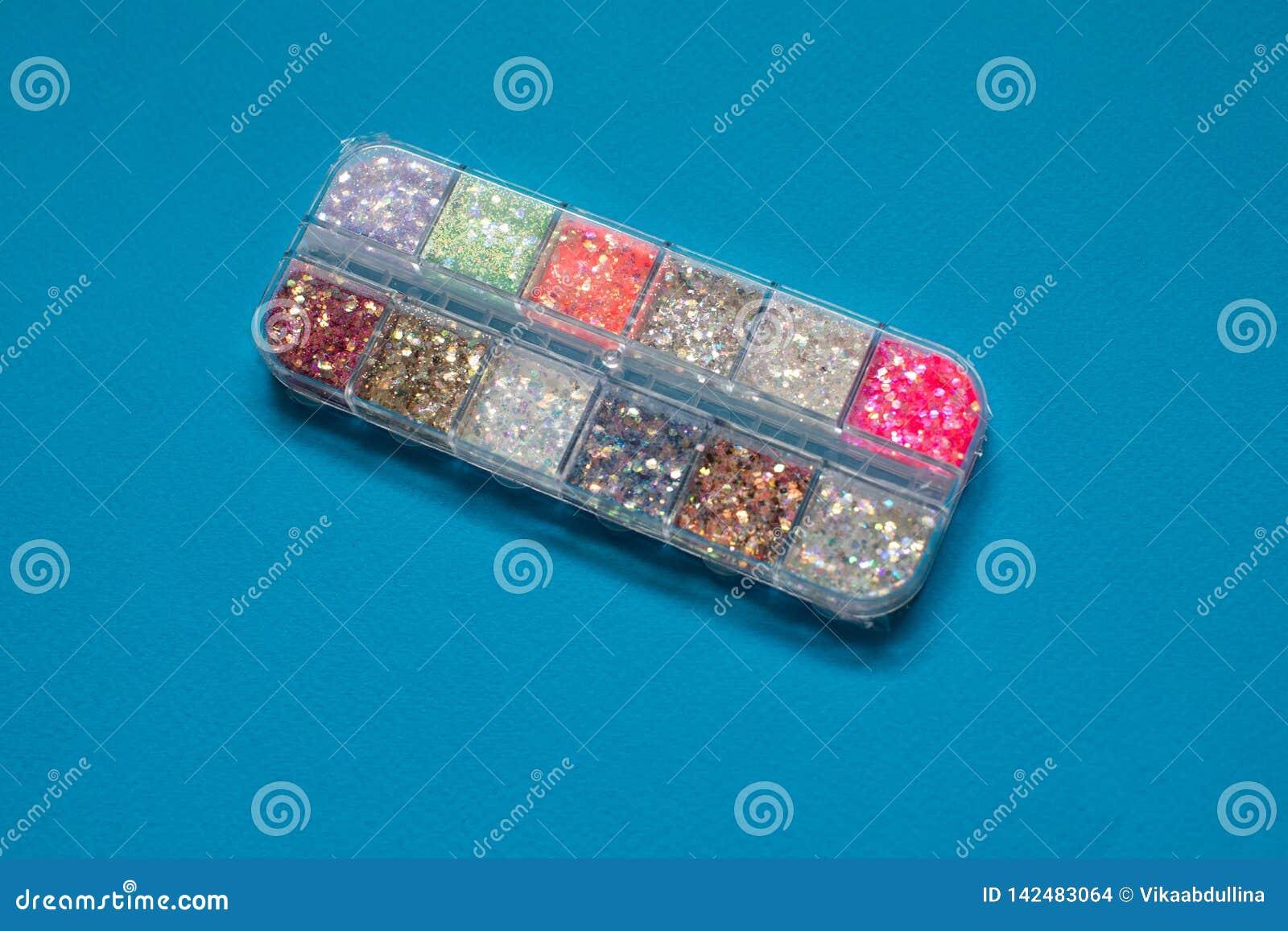 Scintillements colorés pour l art et le maquillage de clou dans le petit conteneur sur le fond bleu