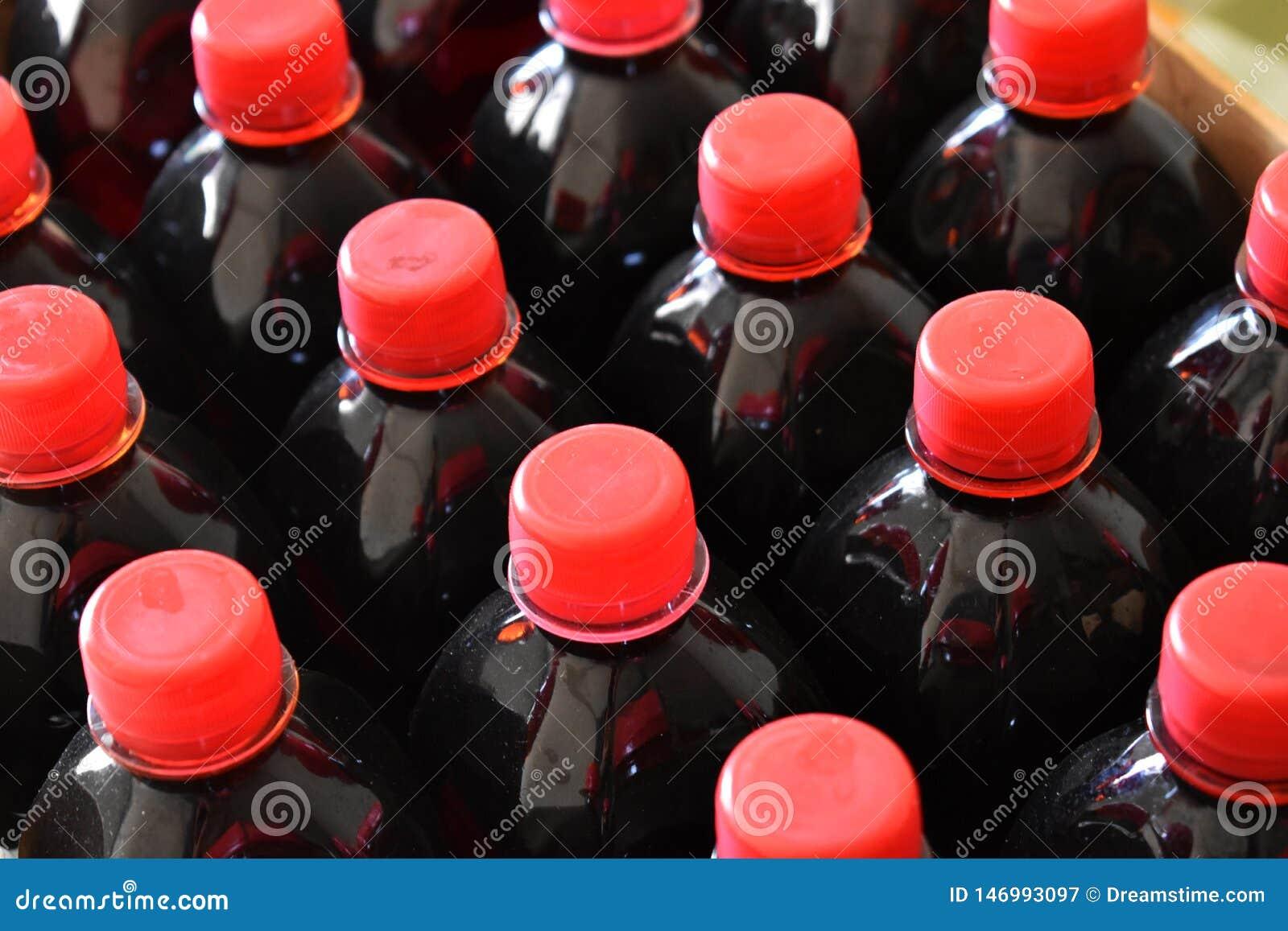 Sciroppo rosso scuro della frutta in bottiglie di plastica
