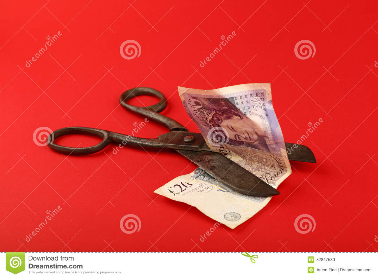 Scissors Cut British Pound Over Red Background Editorial Image