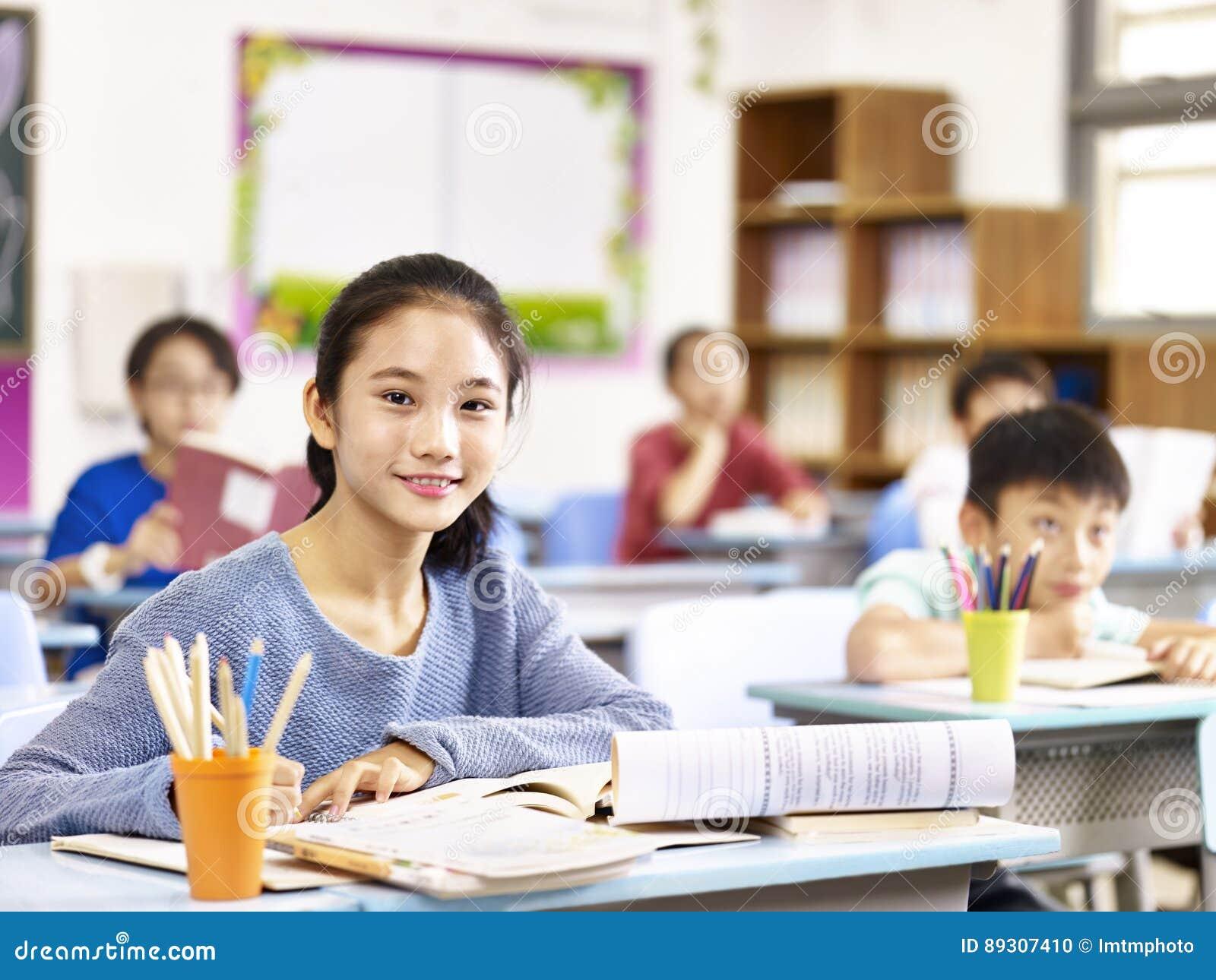 Scolara elementare asiatica nella classe